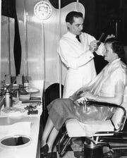 Joseph Weir styles a customer's hair in 1954.