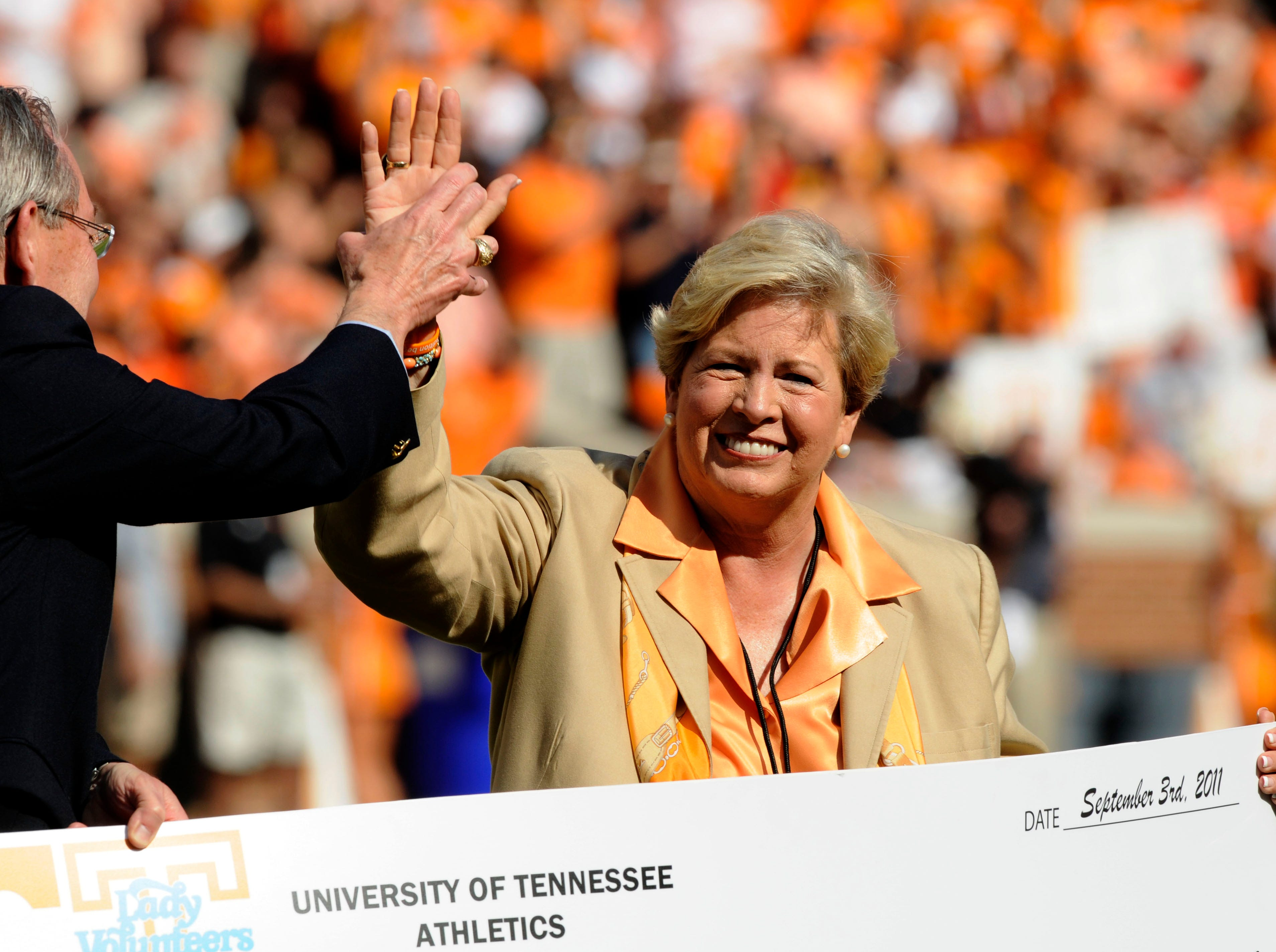 UT Athletics Director Joan Cronan gives a high-five to UT Chancellor Dr. Jimmy Cheek during quick ceremony on the field recognizing her and the athletic department's $5 million donation to the university  Saturday, Sep. 10, 2011 in Neyland Stadium.