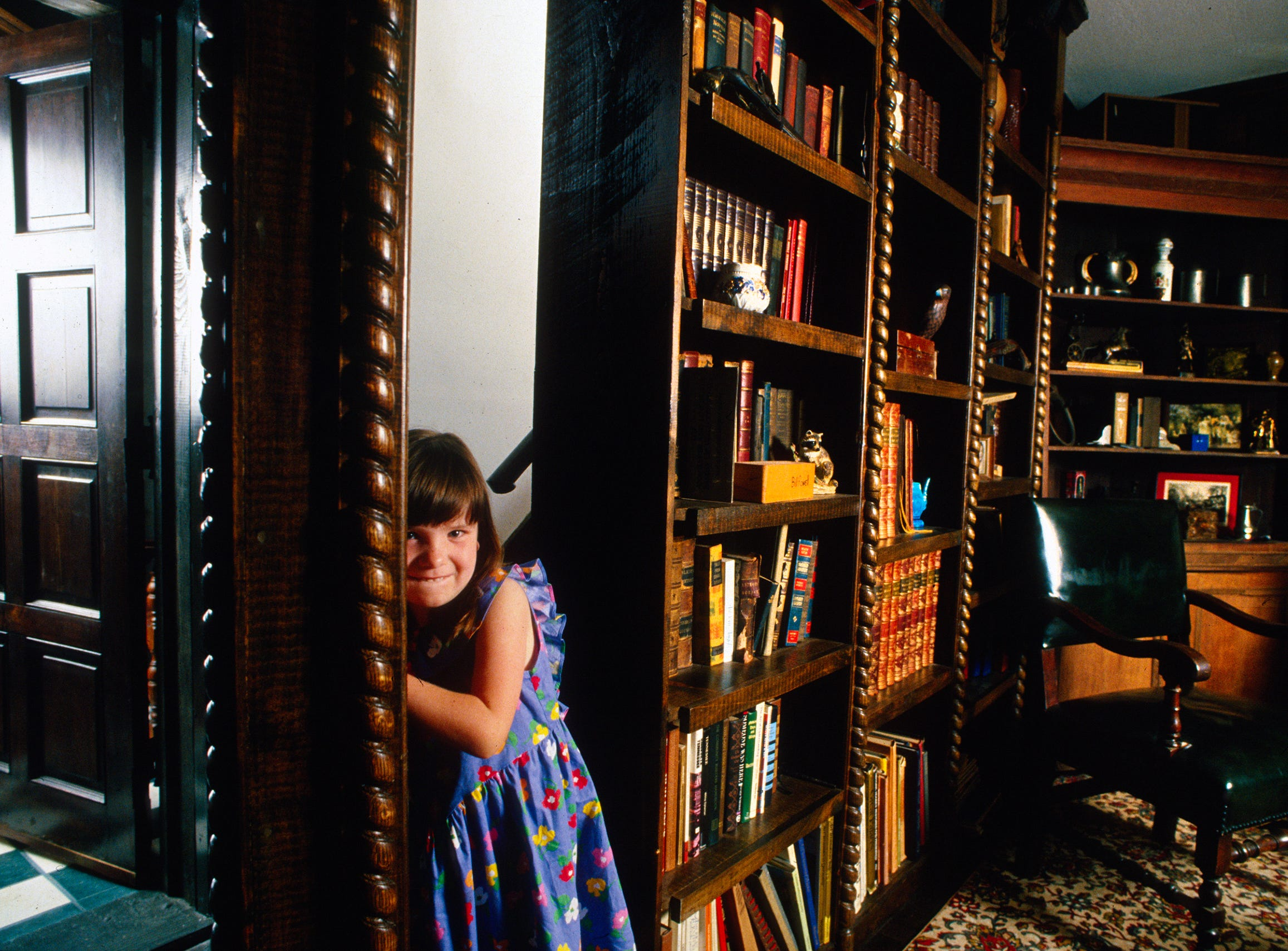 Katie Roy shows a hidden passage behind a bookcase at Williamswood Castle June 16, 1994, in South Knoxville. The 6-year-old is the granddaughter of Williamswood owner Julia Tucker.