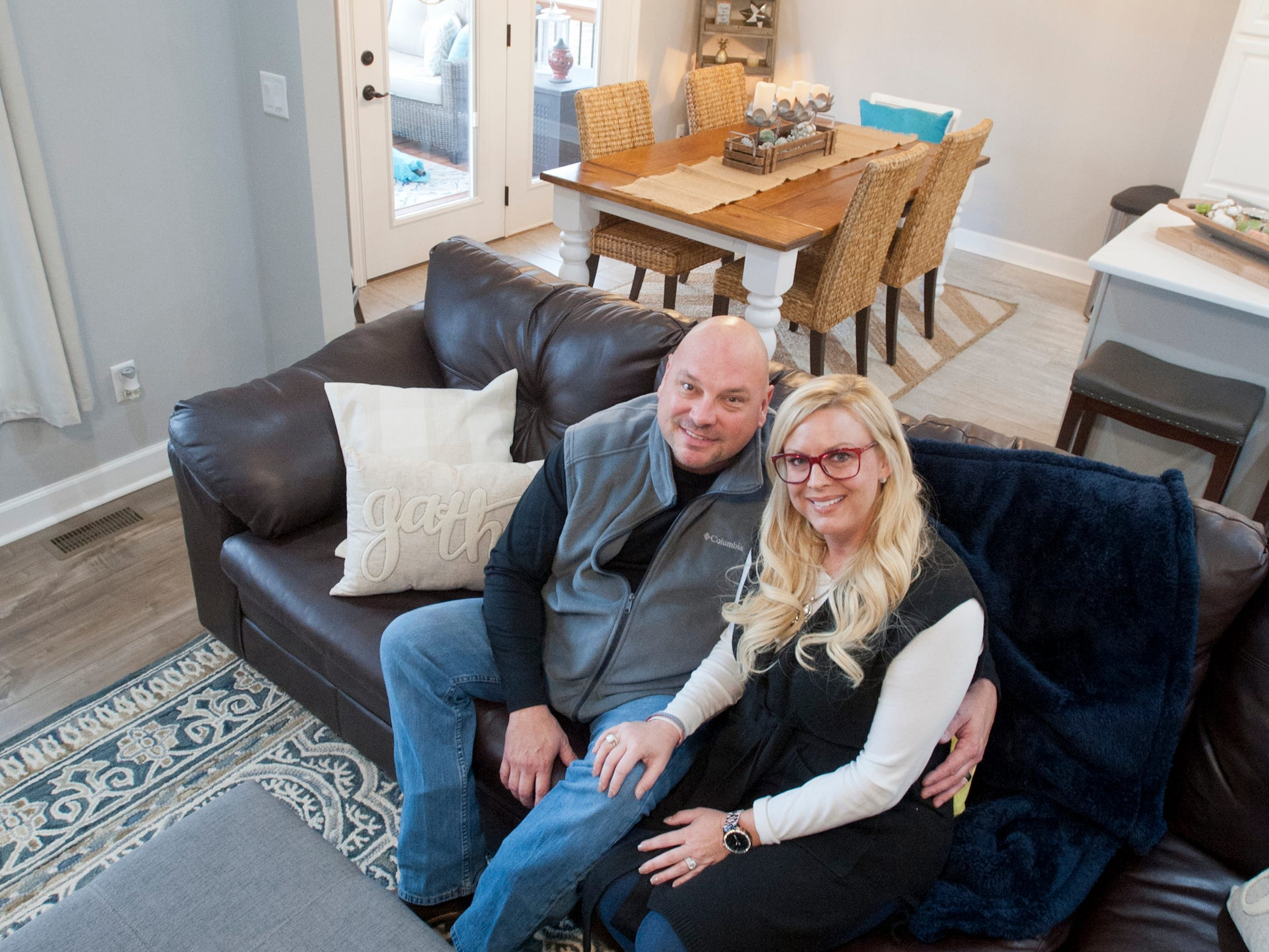 Rick and Sara Bell relax in their first floor living room. Behind them is their open-concept-kitchen dining table.