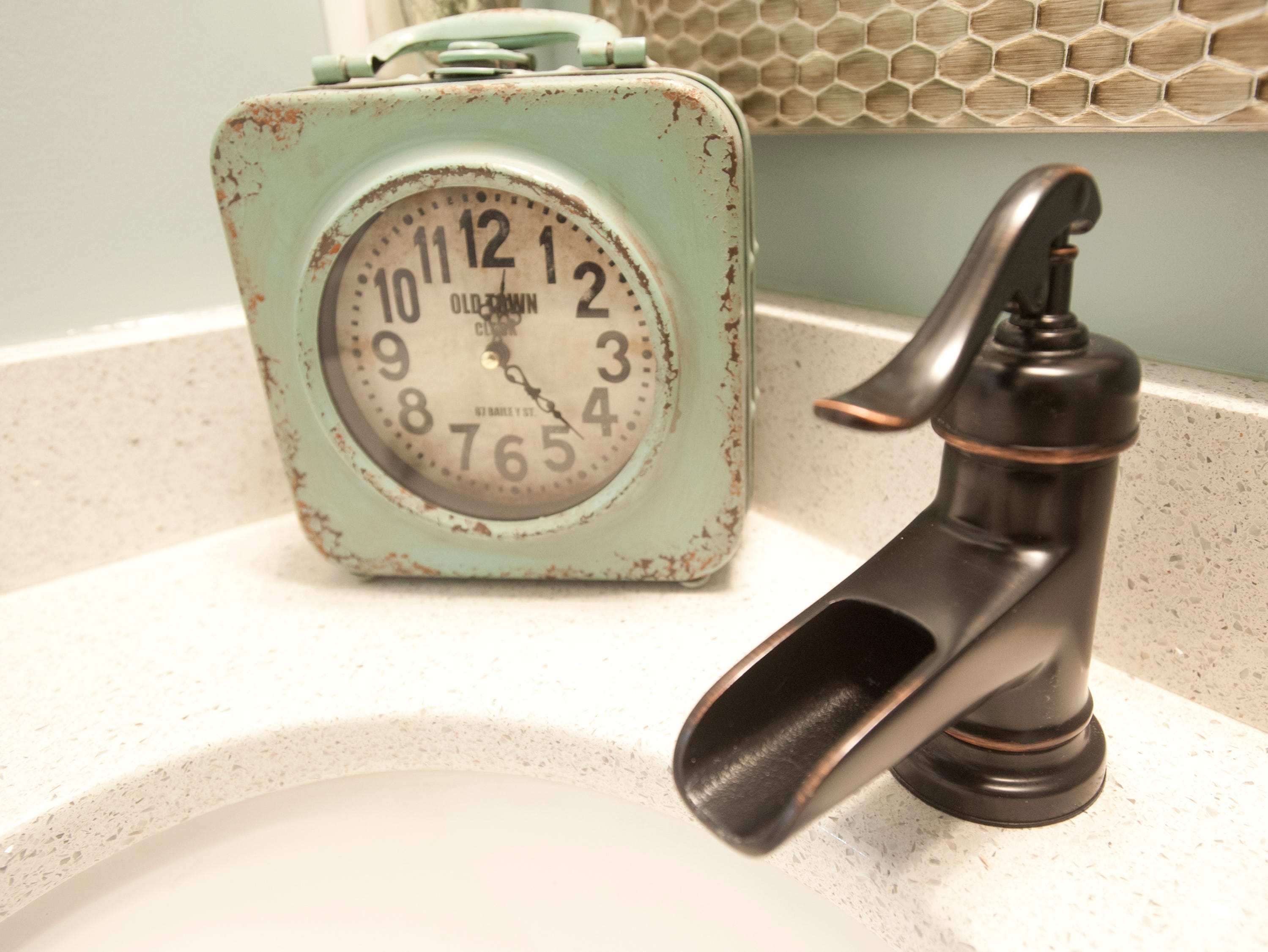 The sinks in the bathrooms employ farm water-pump-styled faucets including this one in the half-bath opposite the mud room. An Old Town Clock decorates the sink.