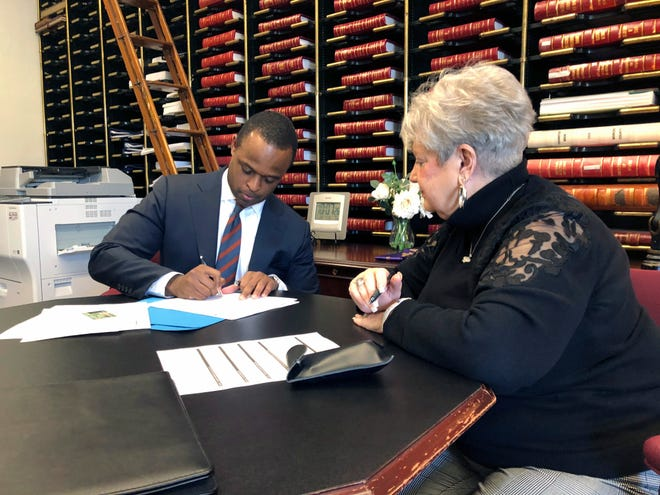 Daniel Cameron, left, a former University of Louisville football player and lawyer for U.S. Senate Majority Leader Mitch McConnell, fills out paperwork with the help of Mary Sue Helm, director of administration and elections for the Secretary of State's Office, to run for Kentucky attorney general, on Tuesday, Jan. 22, 2019, in Frankfort, Kentucky.