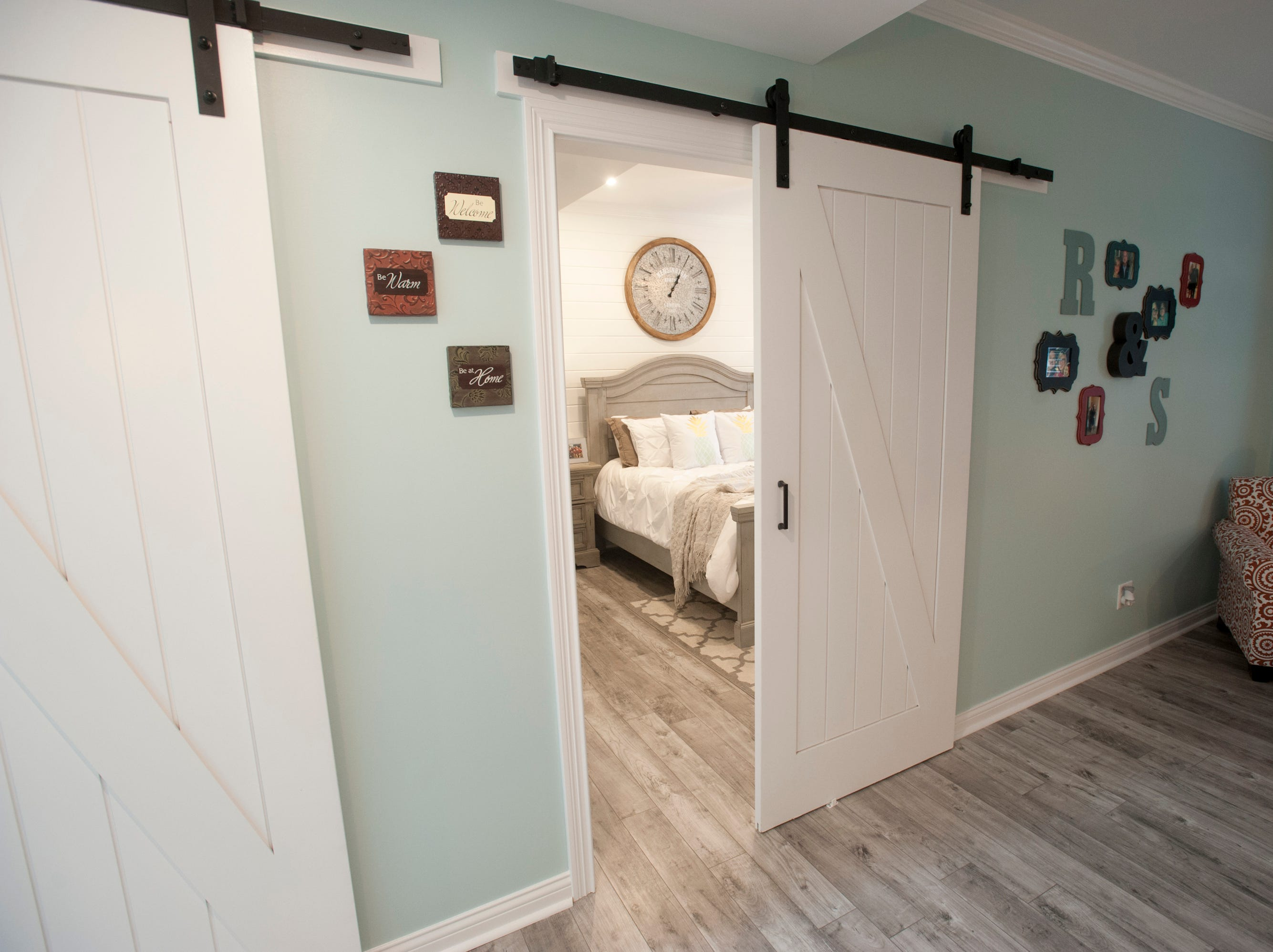 The basement family room entrance of the Bell's daughter's basement workout room, left, and daughter Sarah's bedroom, right, use barn doors..