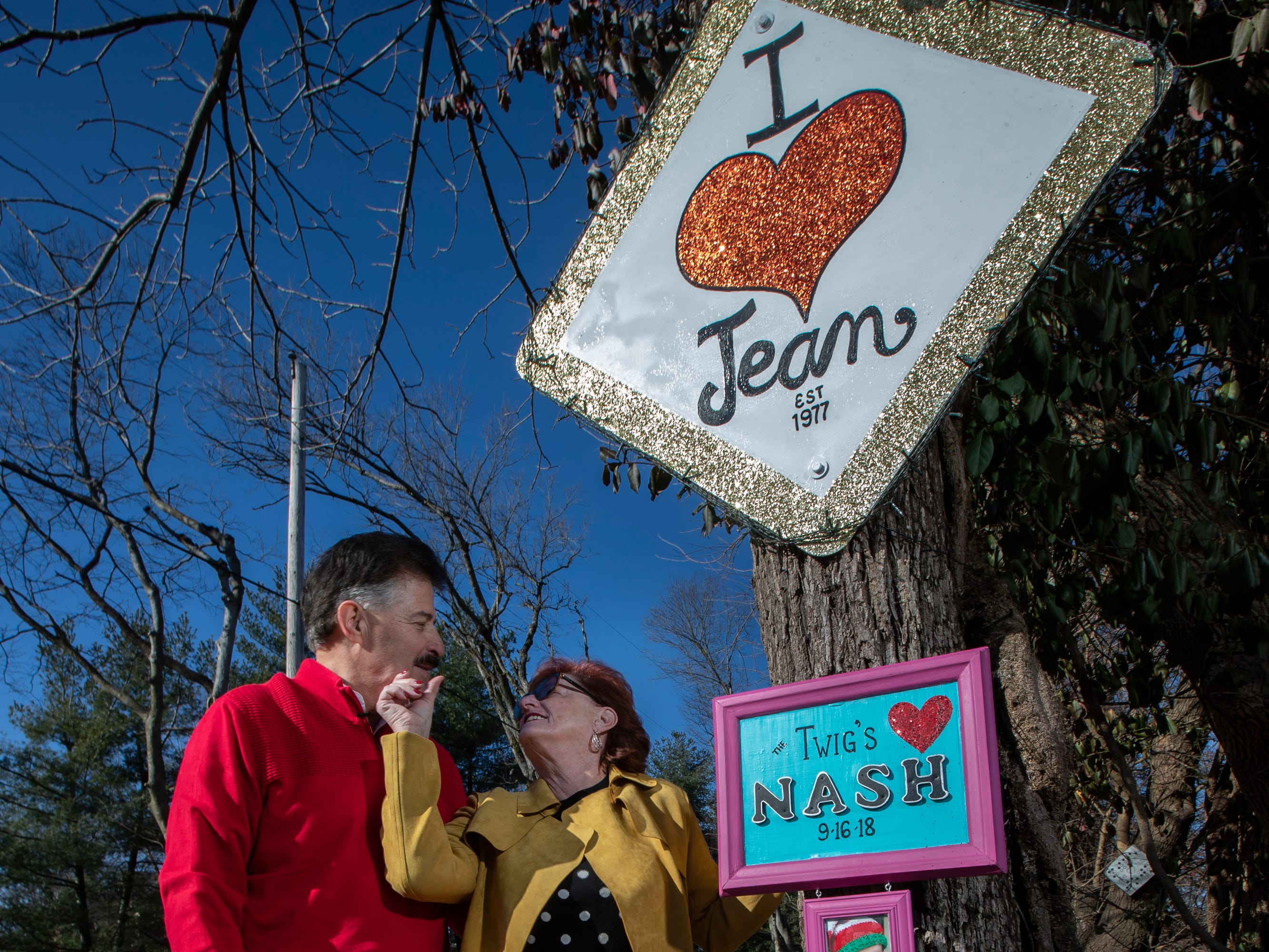 "Jean Terwilleger wipes lipstick from her husband Les' face, as they stand next to their ""I Heart Jean"" sign on the Lover's Lane stretch of Springdale Road. The sign began a trend to place love signs on the road. Jan. 4, 2019"
