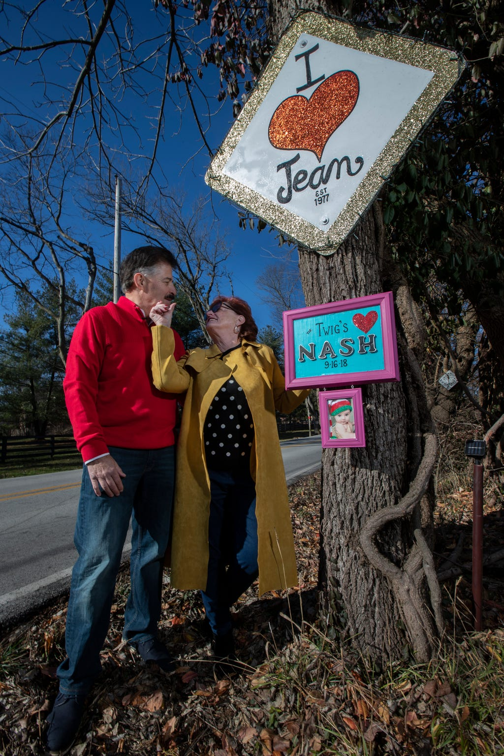"""Jean Terwilleger wipes lipstick from her husband Les' face, as they stand next to their """"I Heart Jean"""" sign on the Lovers Lane."""