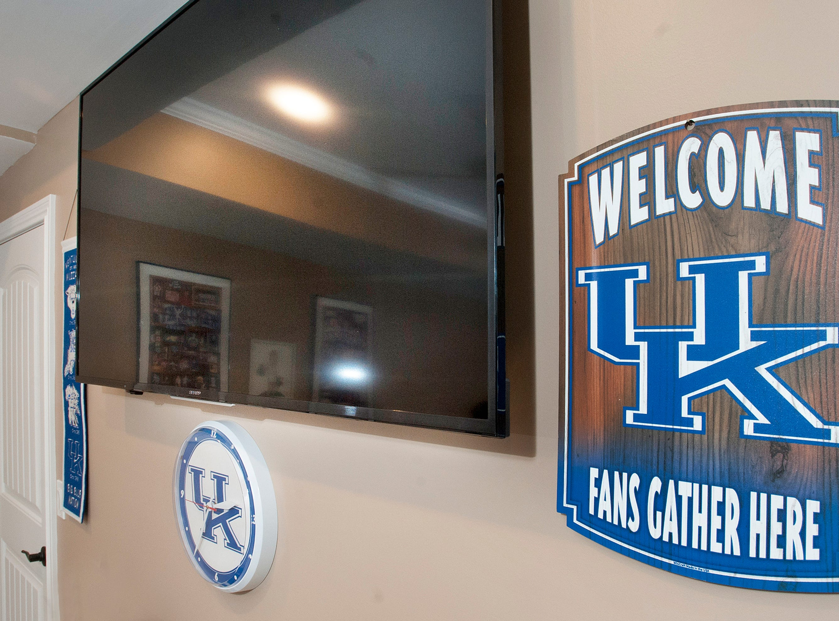"The ""University of Kentucky"" themed workout room in the basement has posters and icons of the team on the walls.