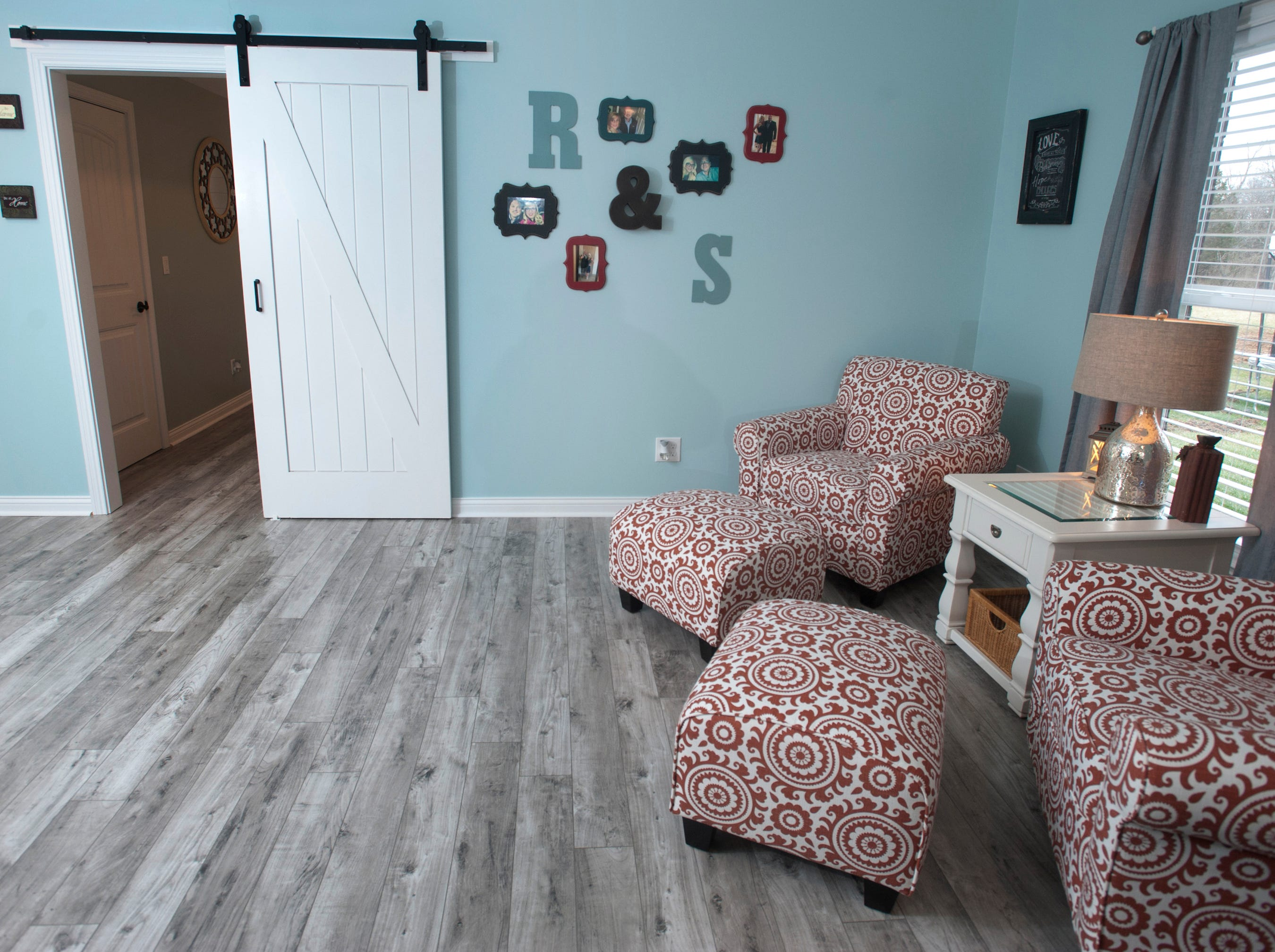 The basement family room. At top left, barn doors are used at the entrance of the Bell's daughter's basement bedroom.