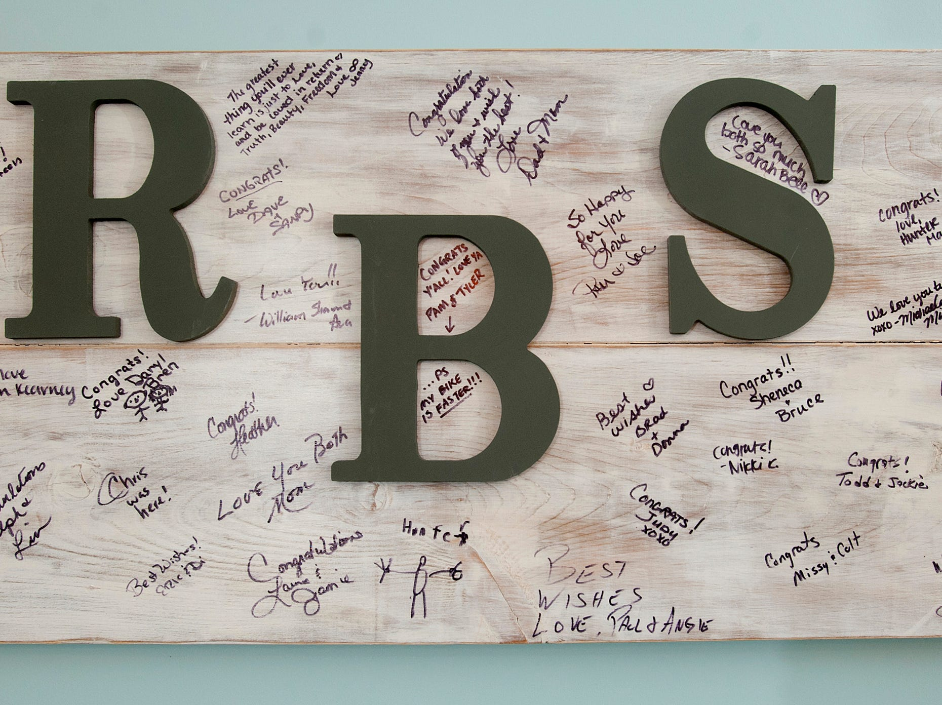 Where many at their wedding have invitees sign a guest book, Rick and Sara Bell had them sign this wedding guest board which hangs in the dining area of the basement.