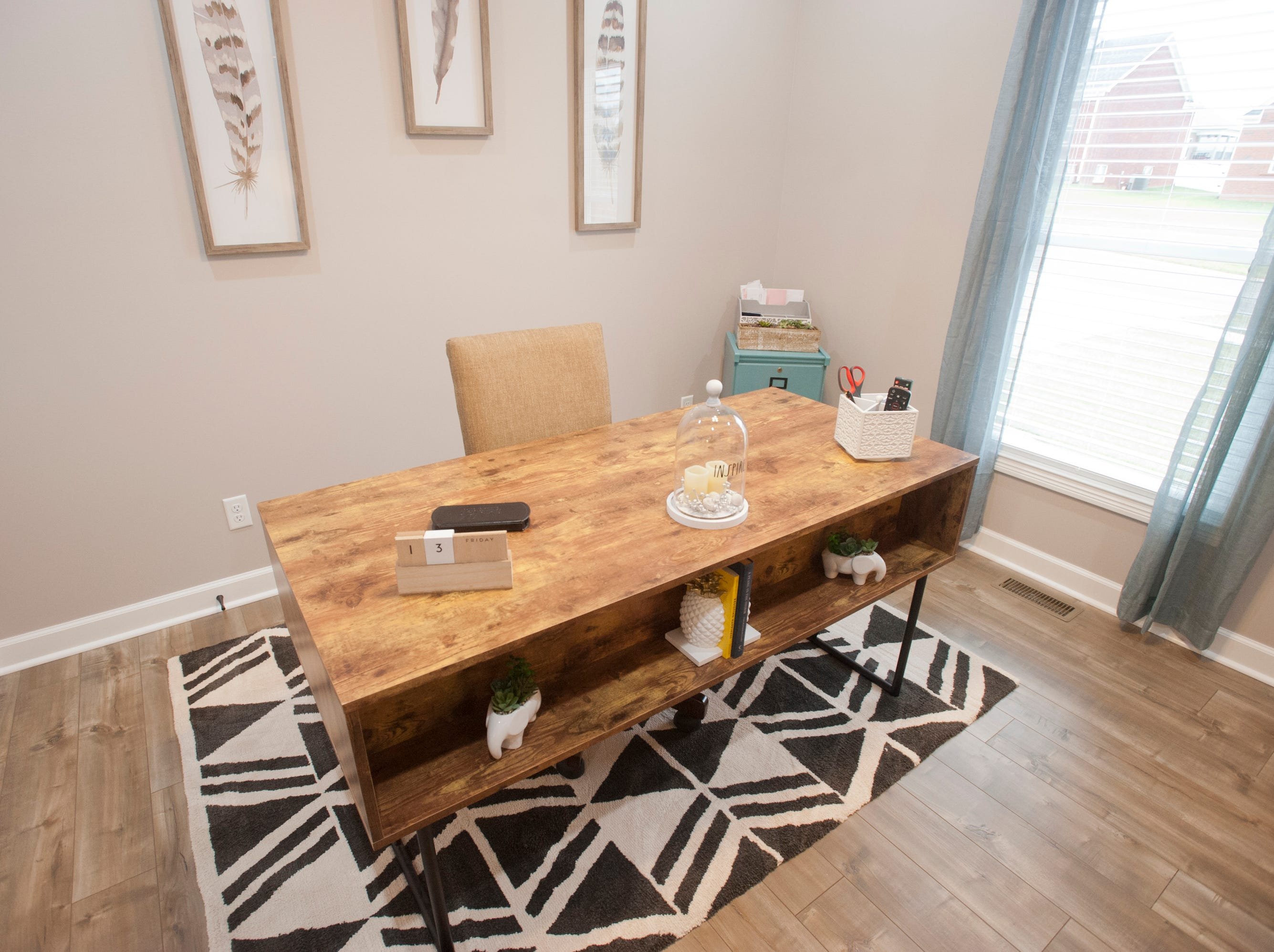 The first-floor office includes an office desk whose front displays artwork. Sara Bell bought the desk at the I Love Fabs furniture store.