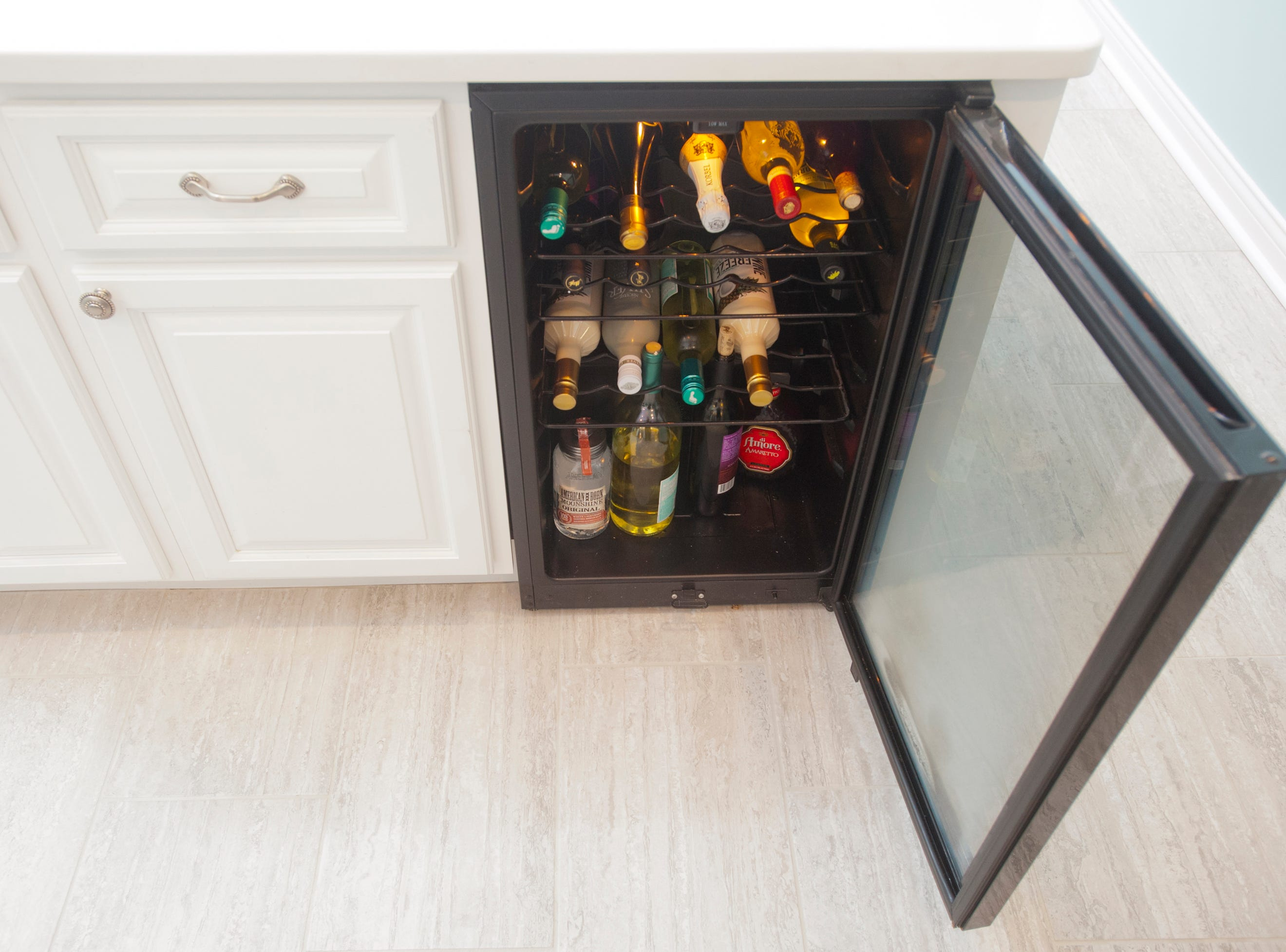 A wine refrigerator is built into the basement kitchen island 