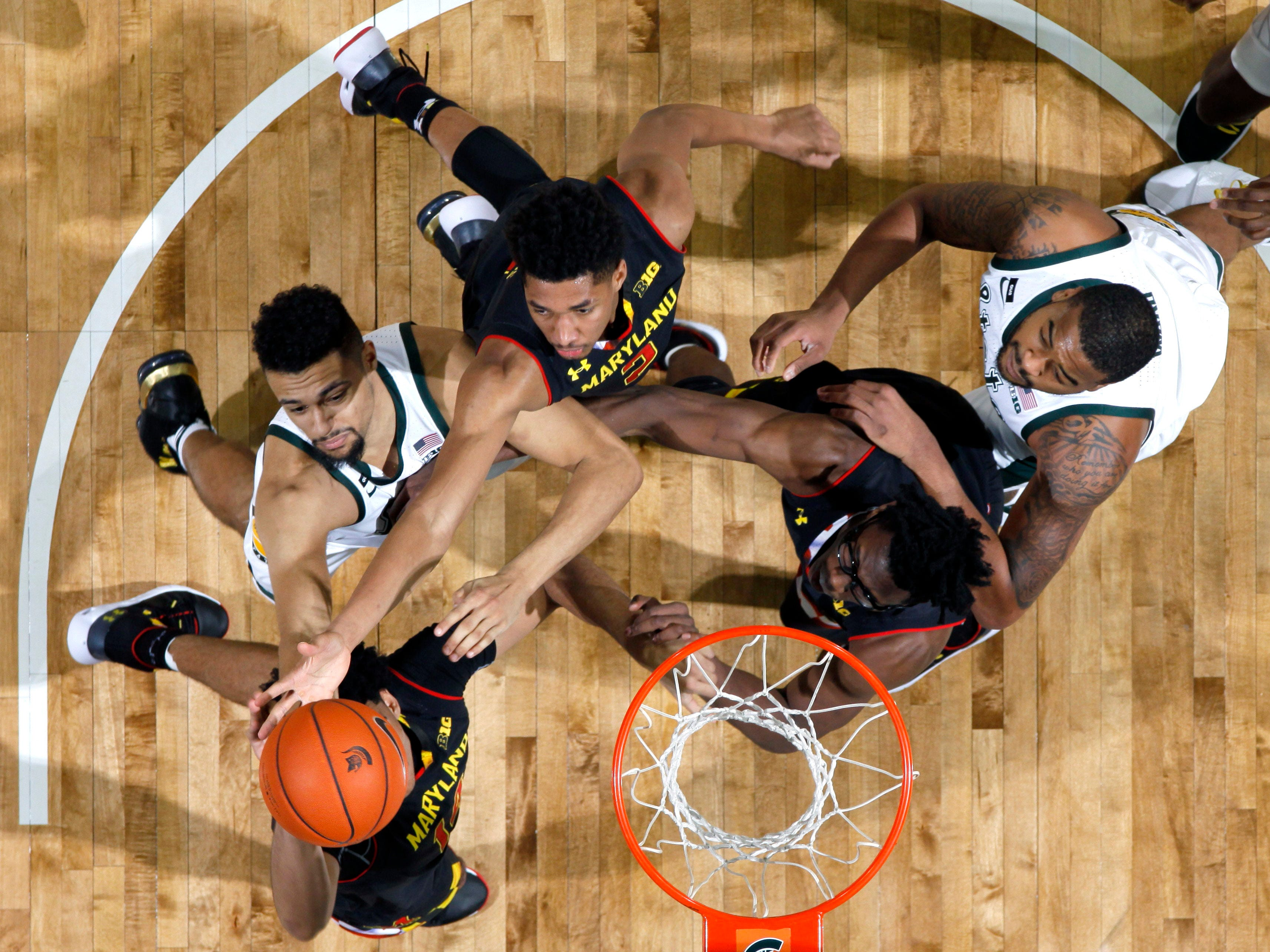 Clockwise from bottom left, Maryland's Ricky Lindo Jr., Michigan State's Kenny Goins, Maryland's Aaron Wiggins and Jalen Smith and Michigan State's Nick Ward vie for a rebound during the second half of an NCAA college basketball game, Monday, Jan. 21, 2019, in East Lansing, Mich. Michigan State won 69-55.
