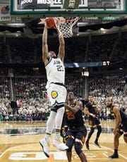 Michigan State Spartans forward Xavier Tillman (23) dunks the ball over Maryland Terrapins forward Jalen Smith (25) during the first half of a game at the Breslin Center.