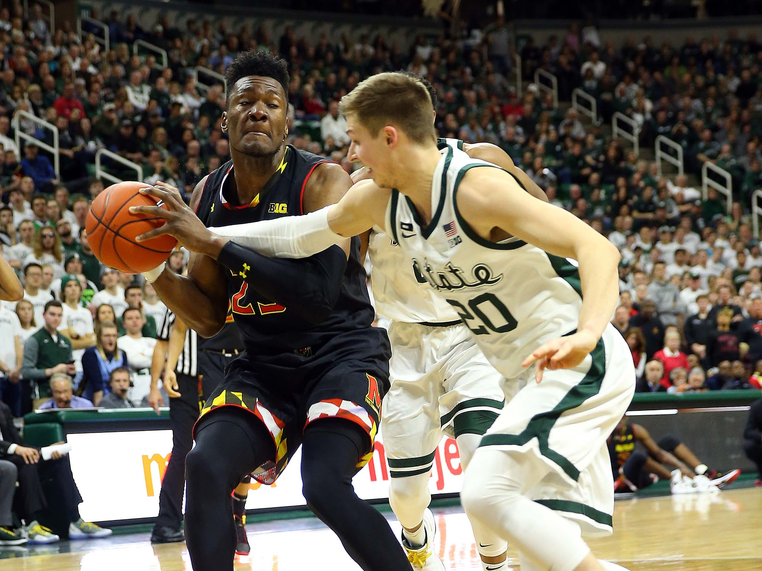 Maryland Terrapins forward Bruno Fernando (23) is fouled by Michigan State Spartans guard Matt McQuaid (20) during the first half of a game at the Breslin Center.