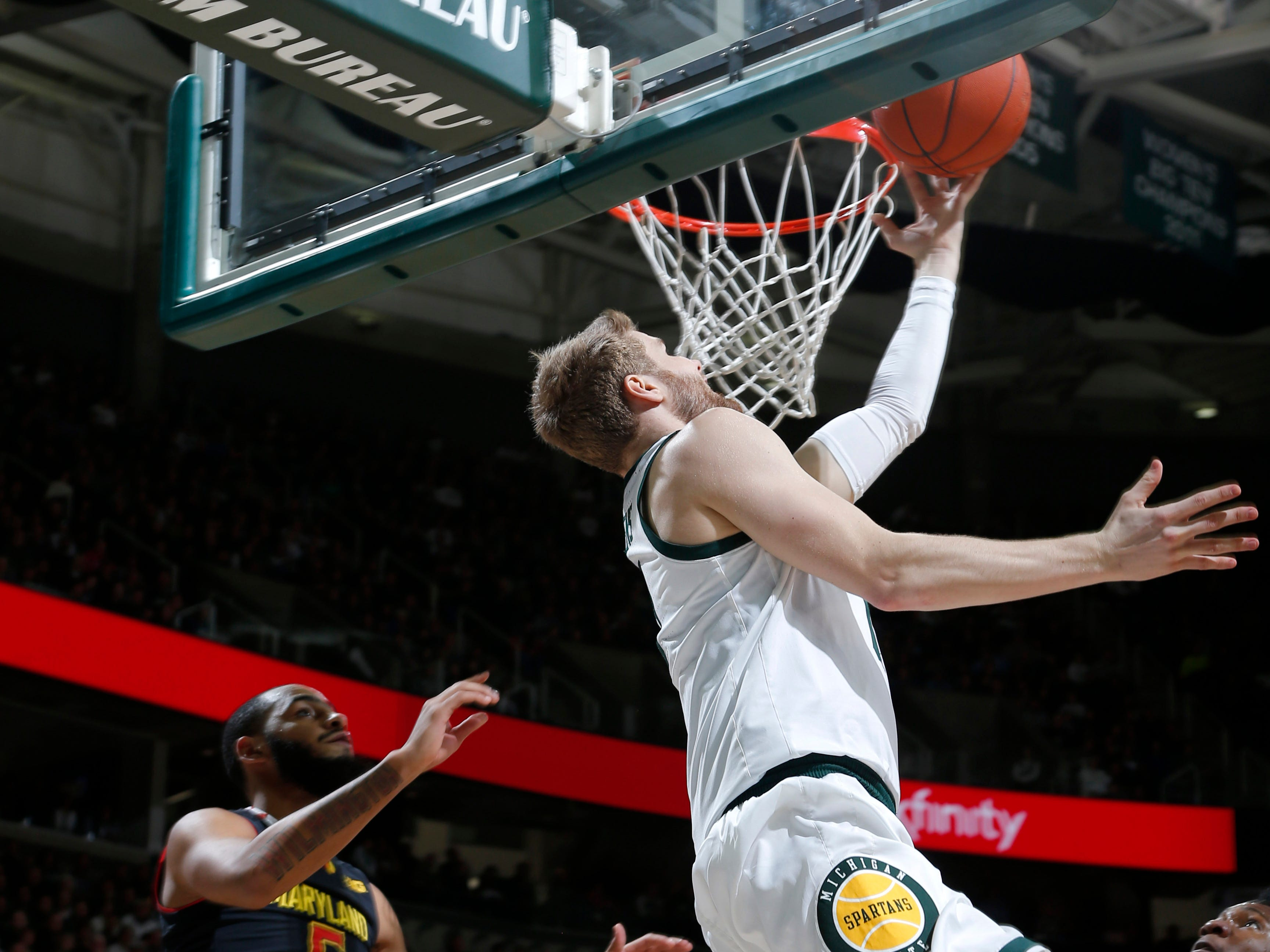 Michigan State's Kyle Ahrens, center, scores on a reverse layup against Maryland's Eric Ayala, left, and Bruno Fernando, right, during the second half of an NCAA college basketball game, Monday, Jan. 21, 2019, in East Lansing, Mich. Michigan State won 69-55.