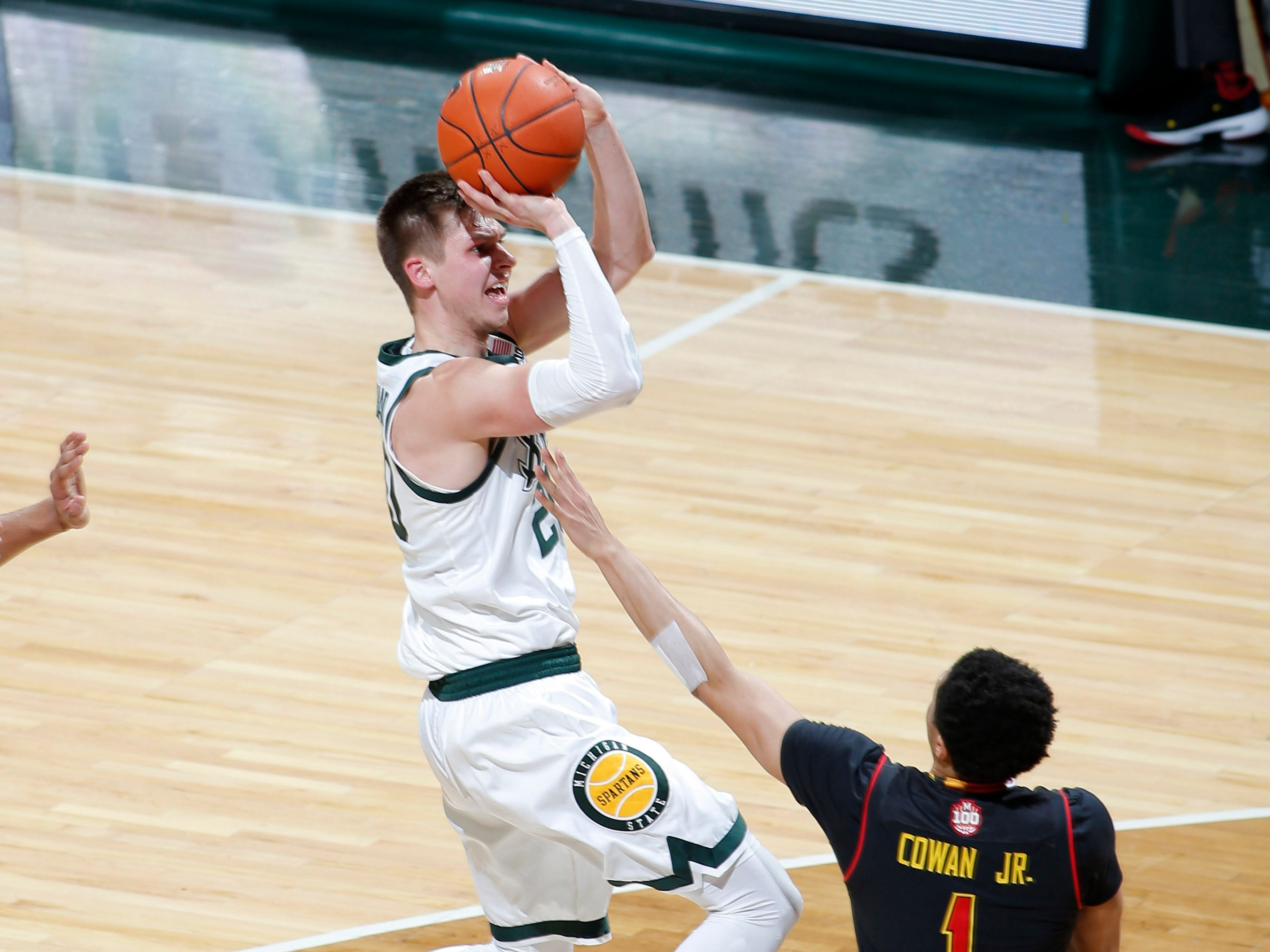 Michigan State's Matt McQuaid, left, shoots against Maryland's Anthony Cowan (1) during the first half of an NCAA college basketball game, Monday, Jan. 21, 2019, in East Lansing, Mich.