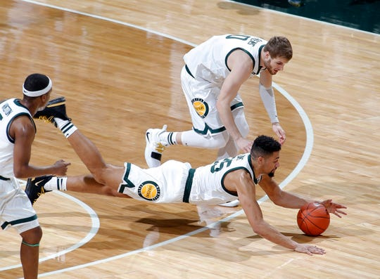 Michigan State's Kenny Goins, bottom, and Kyle Ahrens, top, dive for the ball against Maryland during the first half of an NCAA college basketball game, Monday, Jan. 21, 2019, in East Lansing, Mich. (AP Photo/Al Goldis)