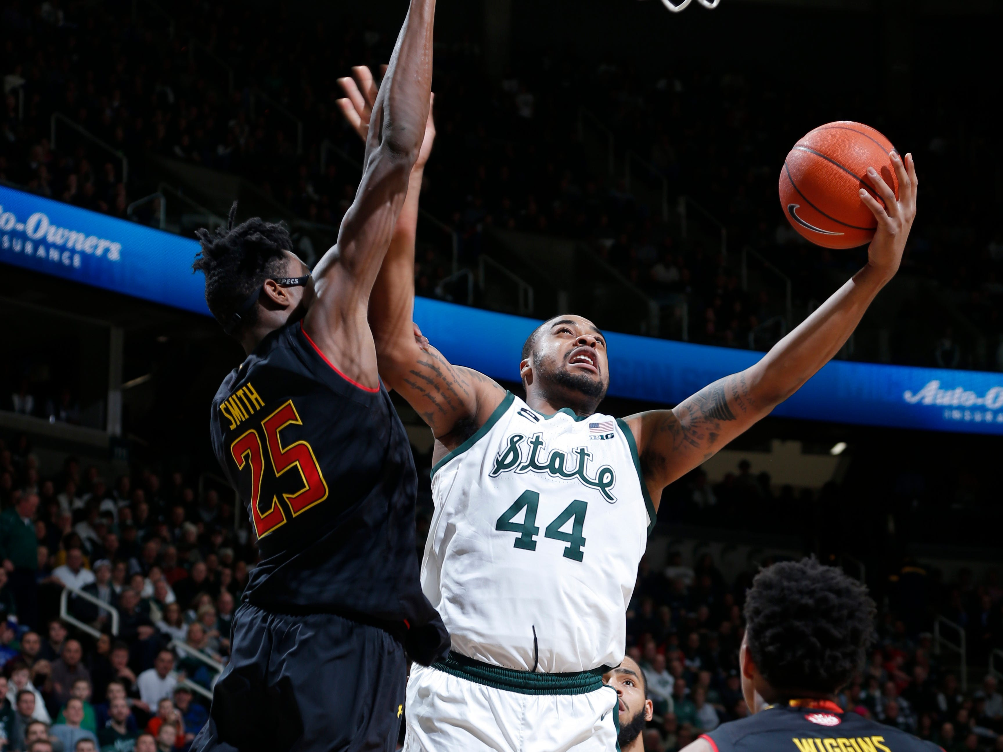Michigan State's Nick Ward, center, puts up a shot against Maryland's Jalen Smith, left, and Aaron Wiggins (2) during the second half of an NCAA college basketball game, Monday, Jan. 21, 2019, in East Lansing, Mich. Michigan State won 69-55.