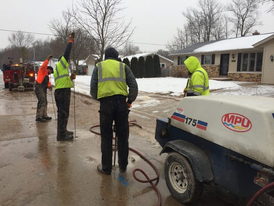 Manitowoc Public Utilities crews work to repair a water main break that caused sewage water to back up into several homes in the 1300 block of Hazelwood Drive early Tuesday.