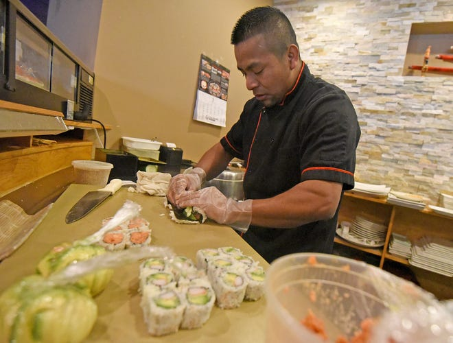 Juan Santiz rolls sushi Tuesday morning during Wokano's grand re-opening ceremony at its new location, 2284 W. Fourth St., Ontario.