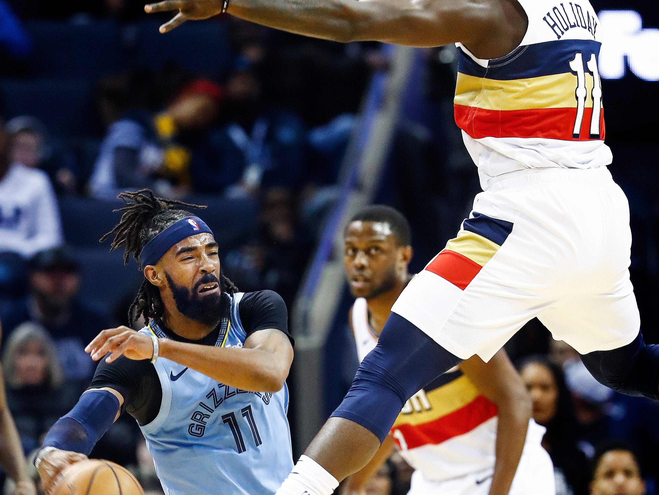Memphis Grizzlies guard Mike Conley (left) tries to make a pass around New Orleans Pelicans defender Jrue Holiday (right) during action at the FedExForum in Memphis, Tenn., Monday, January 21, 2019.