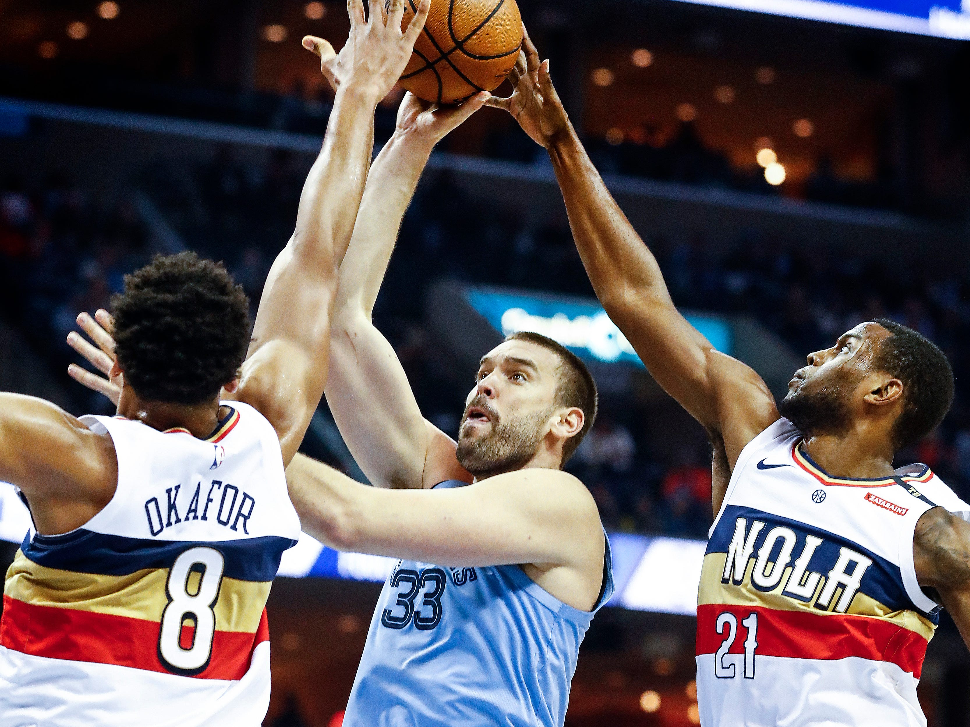 Memphis Grizzlies center Marc Gasol (middle) put up a shot against New Orleans Pelicans defenders Jahlil Okafor (left) and Darius Miller (right) during action at the FedExForum in Memphis, Tenn., Monday, January 21, 2019.
