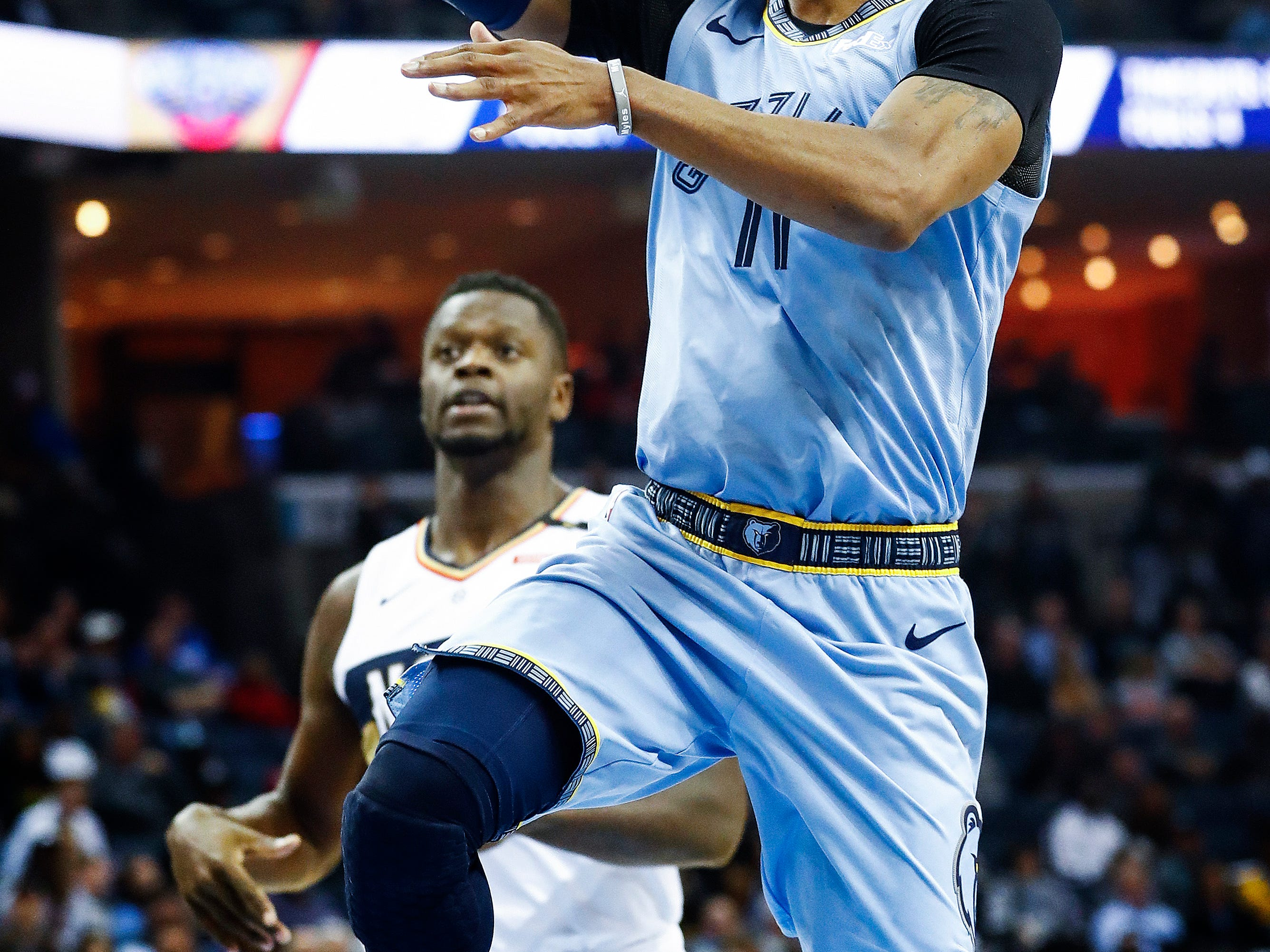 Memphis Grizzlies guard Mike Conley drives for a layup against the New Orleans Pelicans defense during action at the FedExForum in Memphis, Tenn., Monday, January 21, 2019.