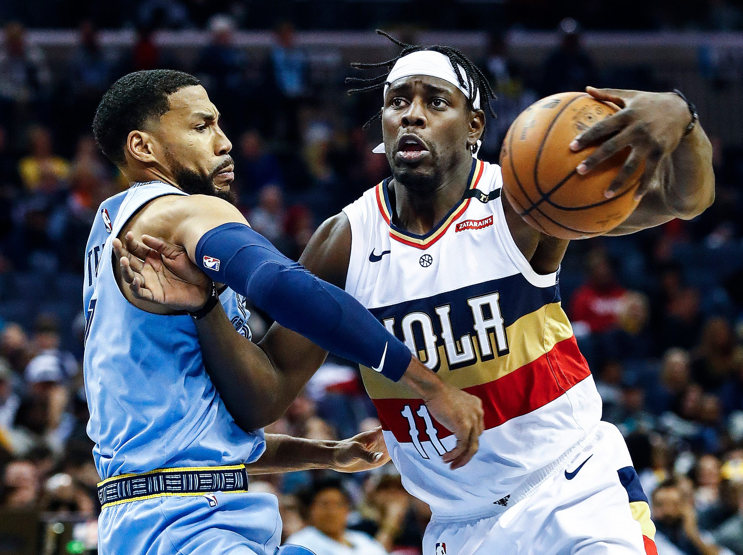 New Orleans Pelicans guard Jrue Holiday (right) drives the lane against Memphis Grizzlies defender Garrett Temple (left) during action at the FedExForum in Memphis, Tenn., Monday, January 21, 2019.