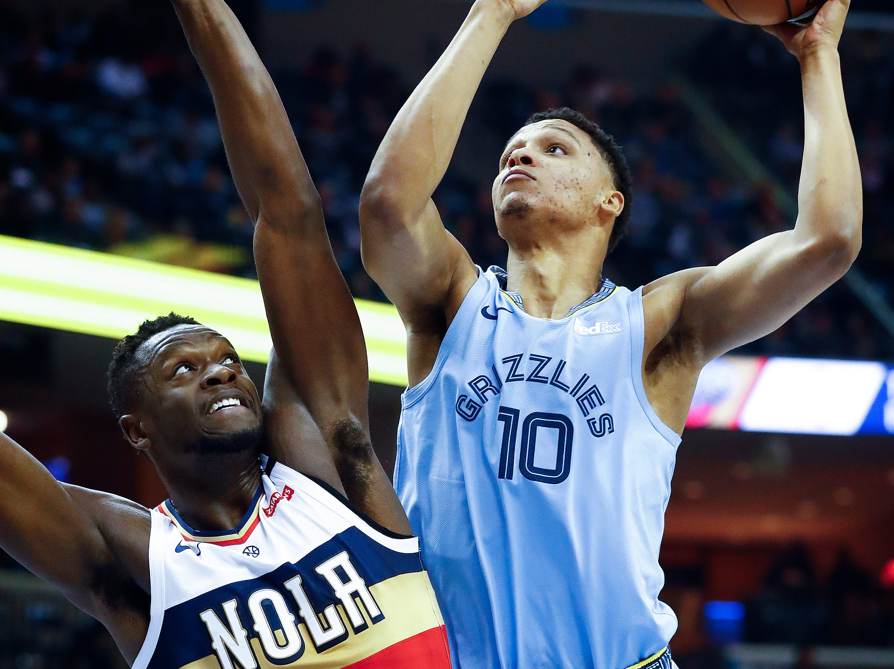 Memphis Grizzlies forward Ivan Rabb (right) hits a shot over New Orleans Pelicans defender Julius Randle (left) during action at the FedExForum in Memphis, Tenn., Monday, January 21, 2019.