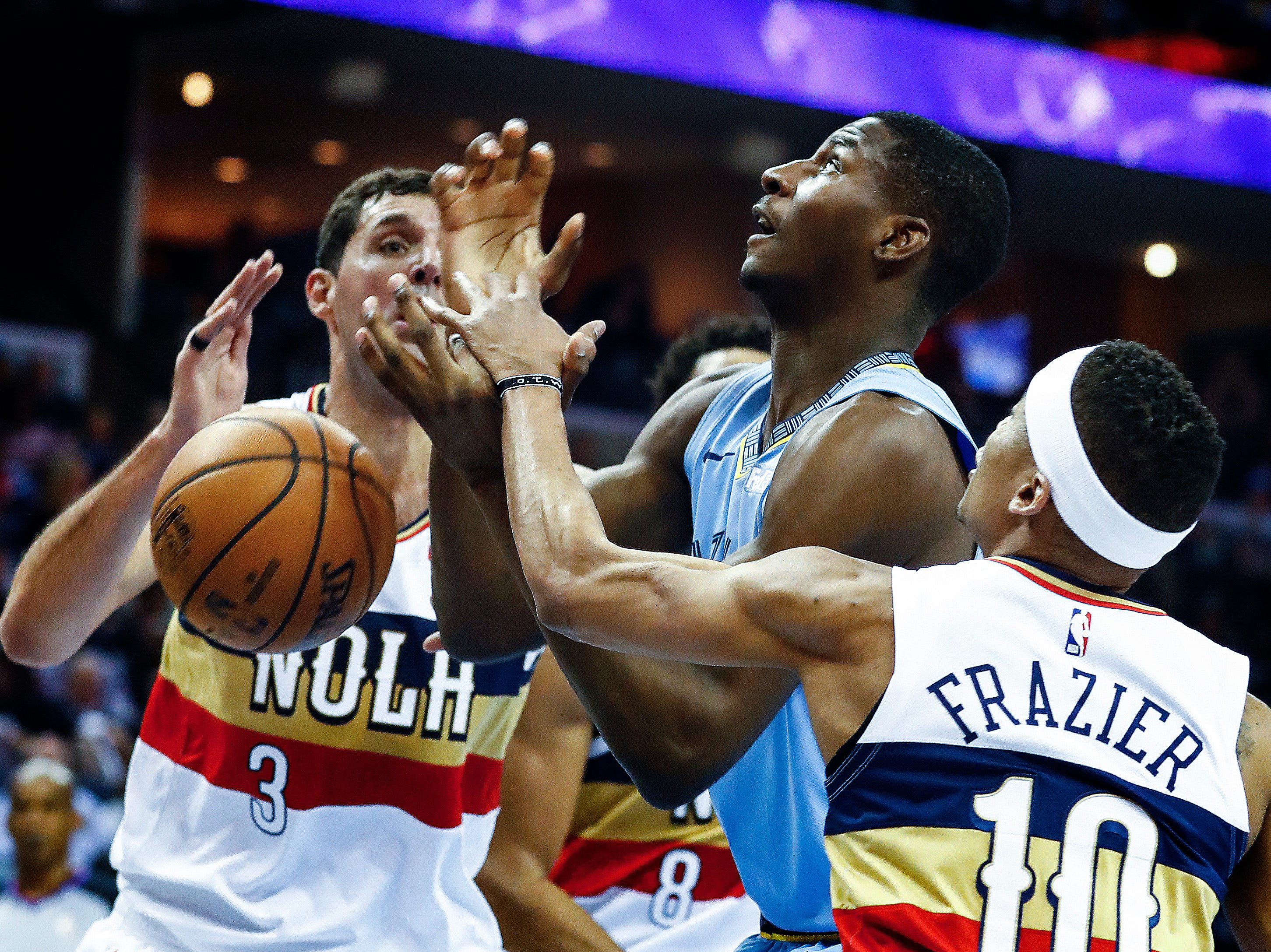 Memphis Grizzlies center Jaren Jackson Jr. (middle) has the ball stripped while guarded by New Orleans Pelicans defenders Nikola Mirotic (left) and Tim Frazier (right) during action at the FedExForum in Memphis, Tenn., Monday, January 21, 2019.