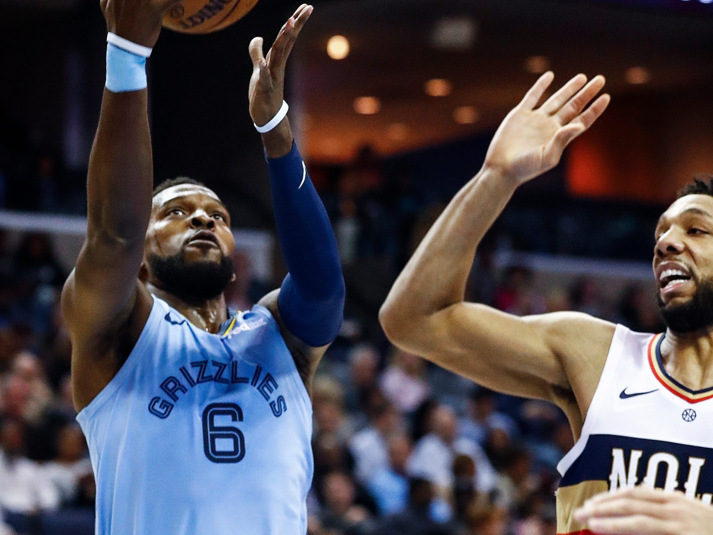 Memphis Grizzlies guard Shelvin Mack (left) drives for a layup against New Orleans Pelicans defender Jahlil Okafor (right) during action at the FedExForum in Memphis, Tenn., Monday, January 21, 2019.