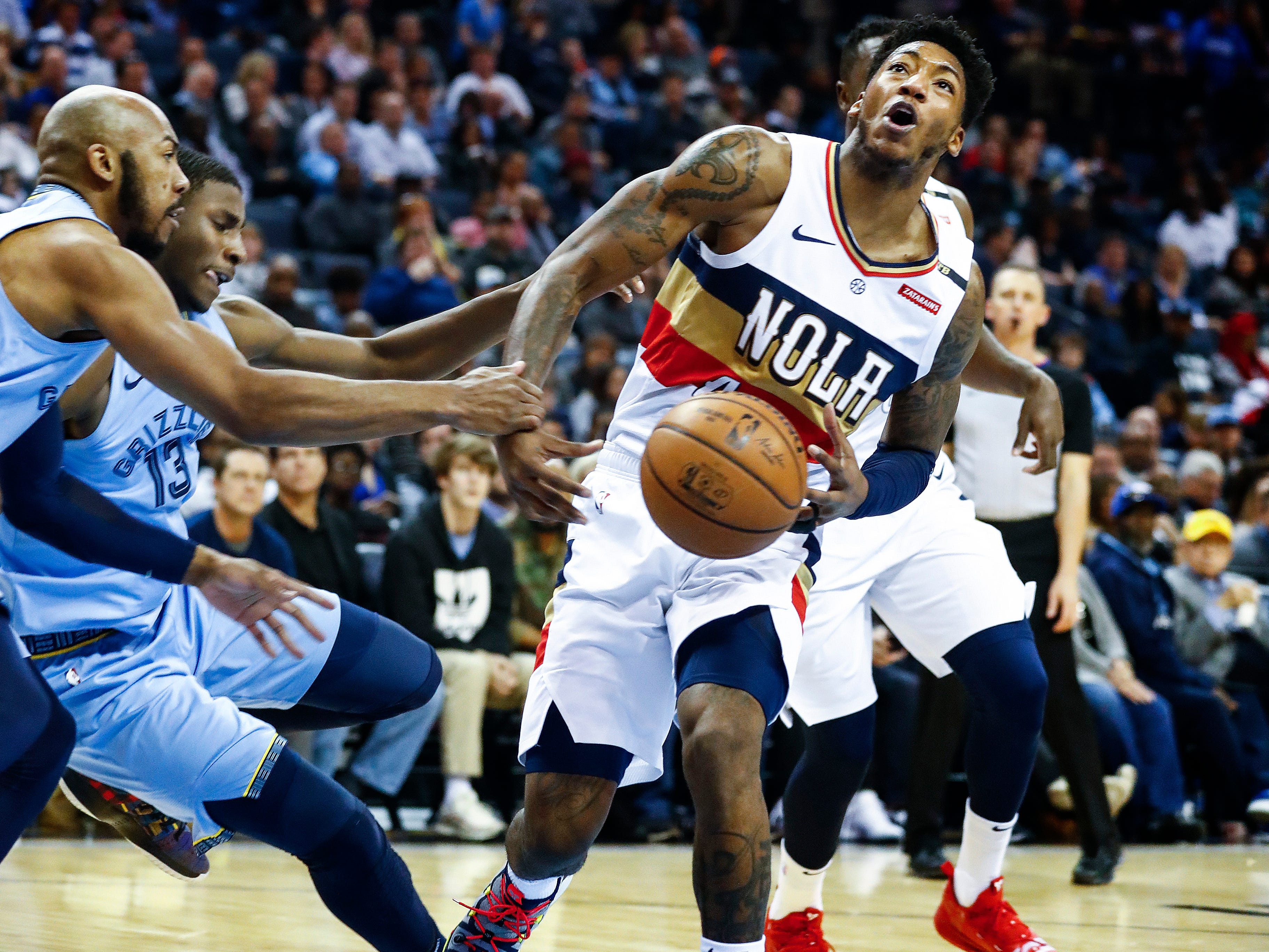 New Orleans Pelicans guard Elfrid Payton (right) is fouled while driving the lane against Memphis Grizzlies defenders Jevon Carter (left) and Jaren Jackson Jr. (middle) during action at the FedExForum in Memphis, Tenn., Monday, January 21, 2019.