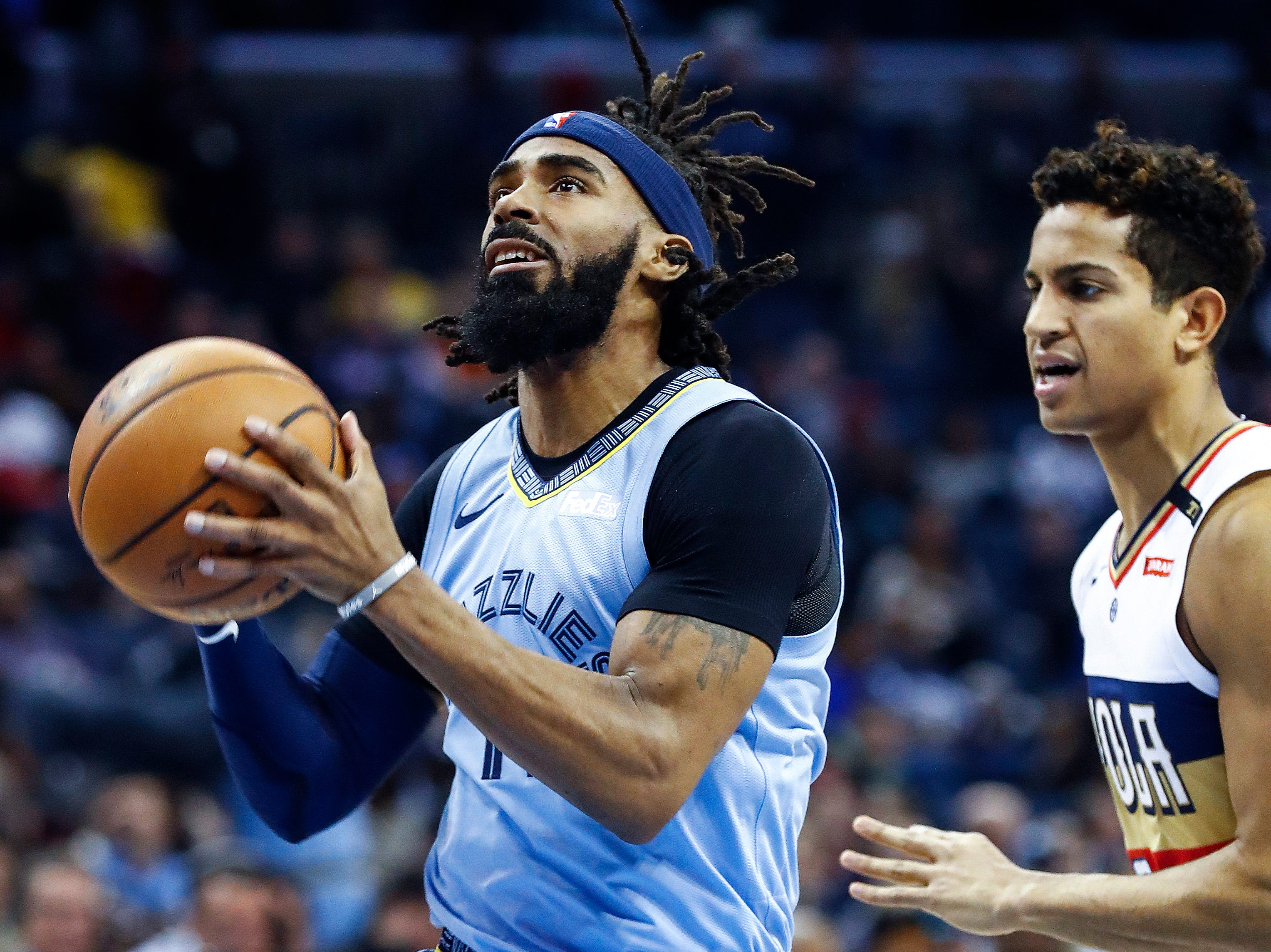Memphis Grizzlies guard Mike Conley (left) drives the lane against New Orleans Pelicans defender Frank Jackson (right) during action at the FedExForum in Memphis, Tenn., Monday, January 21, 2019.