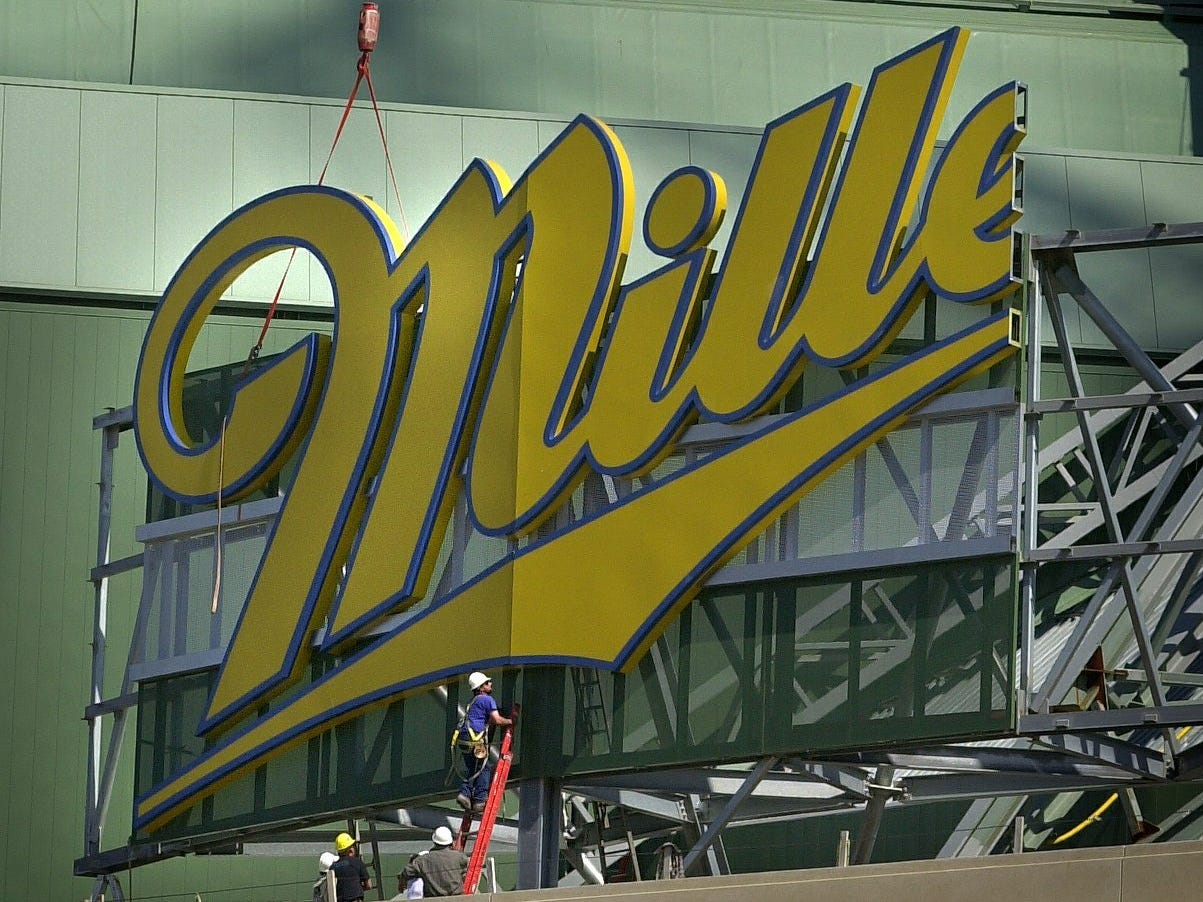 Workers begin putting up two sections of the Miller Park sign at the front of the new stadium Thursday, April 27, 2000.