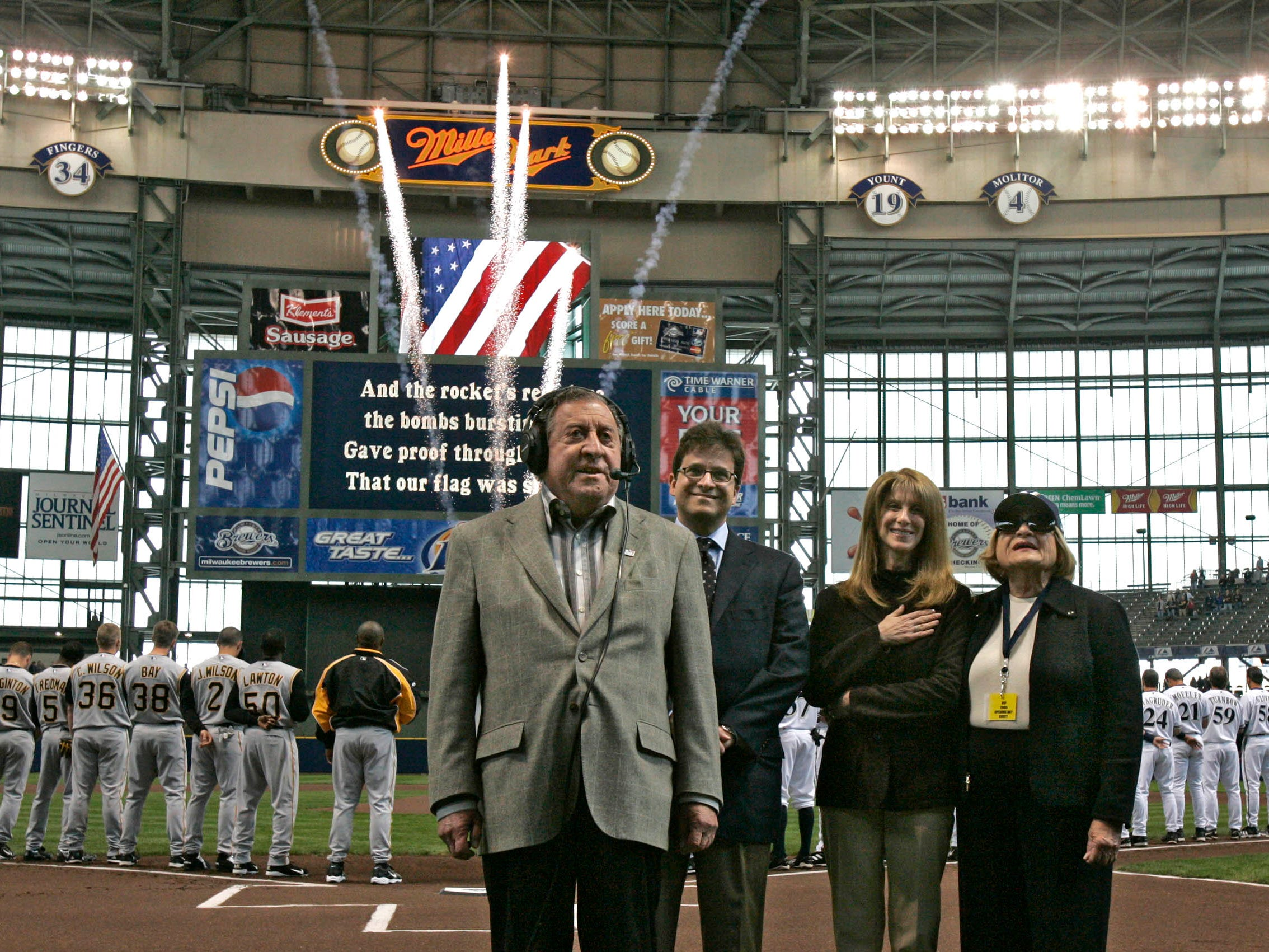 Joseph Attanasio sings the national anthem at Miller Park during the home opener Monday, April 11, 2005, with new Brewers owner and son, Mark; Mark's wife, Debbie; and his wife, Connie, by his side.