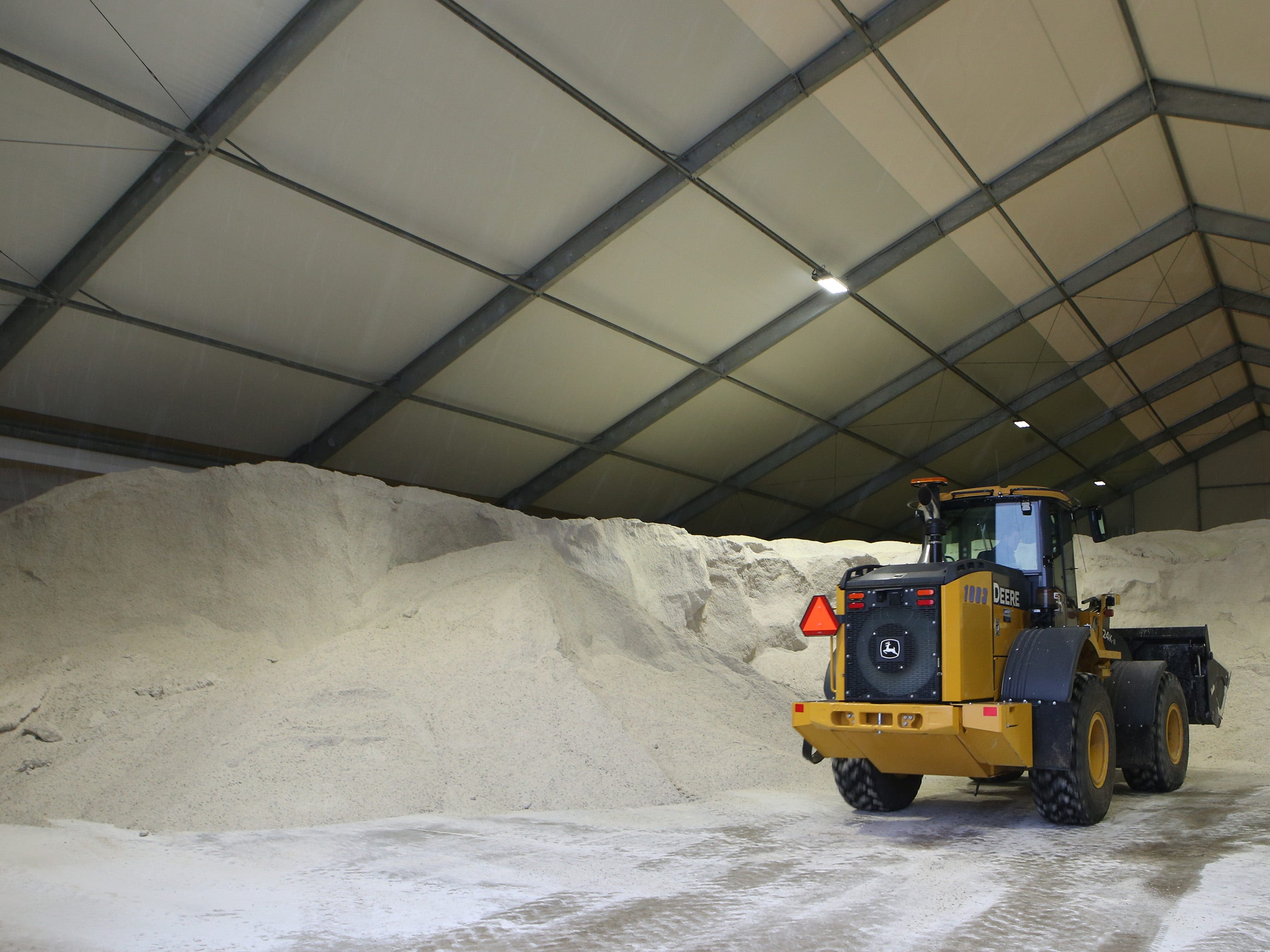 Road salt is scooped from an enclosed storage area at the Public Works Yard on Good Home Road as snow from the Jan. 22 snowstorm begins to fall. A typical eight ton salt load lasts about one hour of driving one of the Village's snow clearing and salting routes.