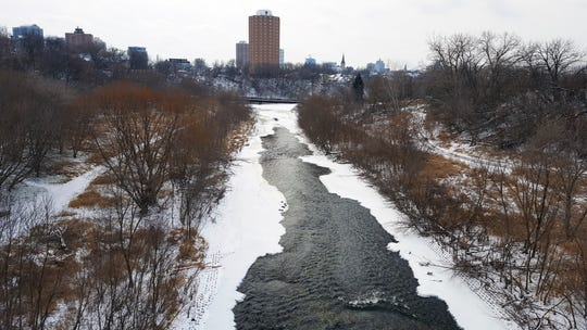 The Milwaukee River flows through a snowy landscape south of North Ave. in Milwaukee on Dec. 29, 2017.