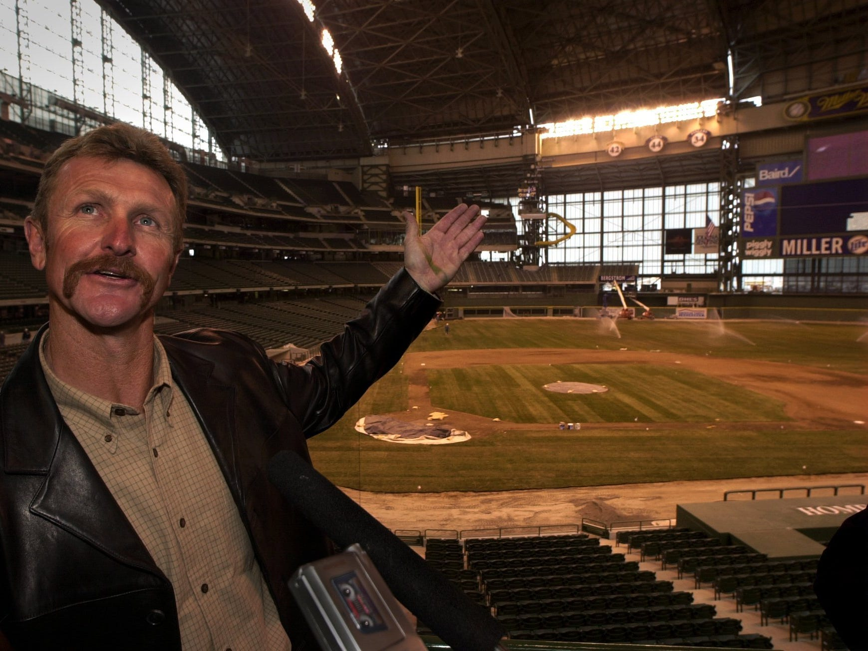 Wearing a stripe of green paint on his hand from touching a freshly painted handrail, former Milwaukee Brewers player Robin Yount admires the inside of Miller Park.