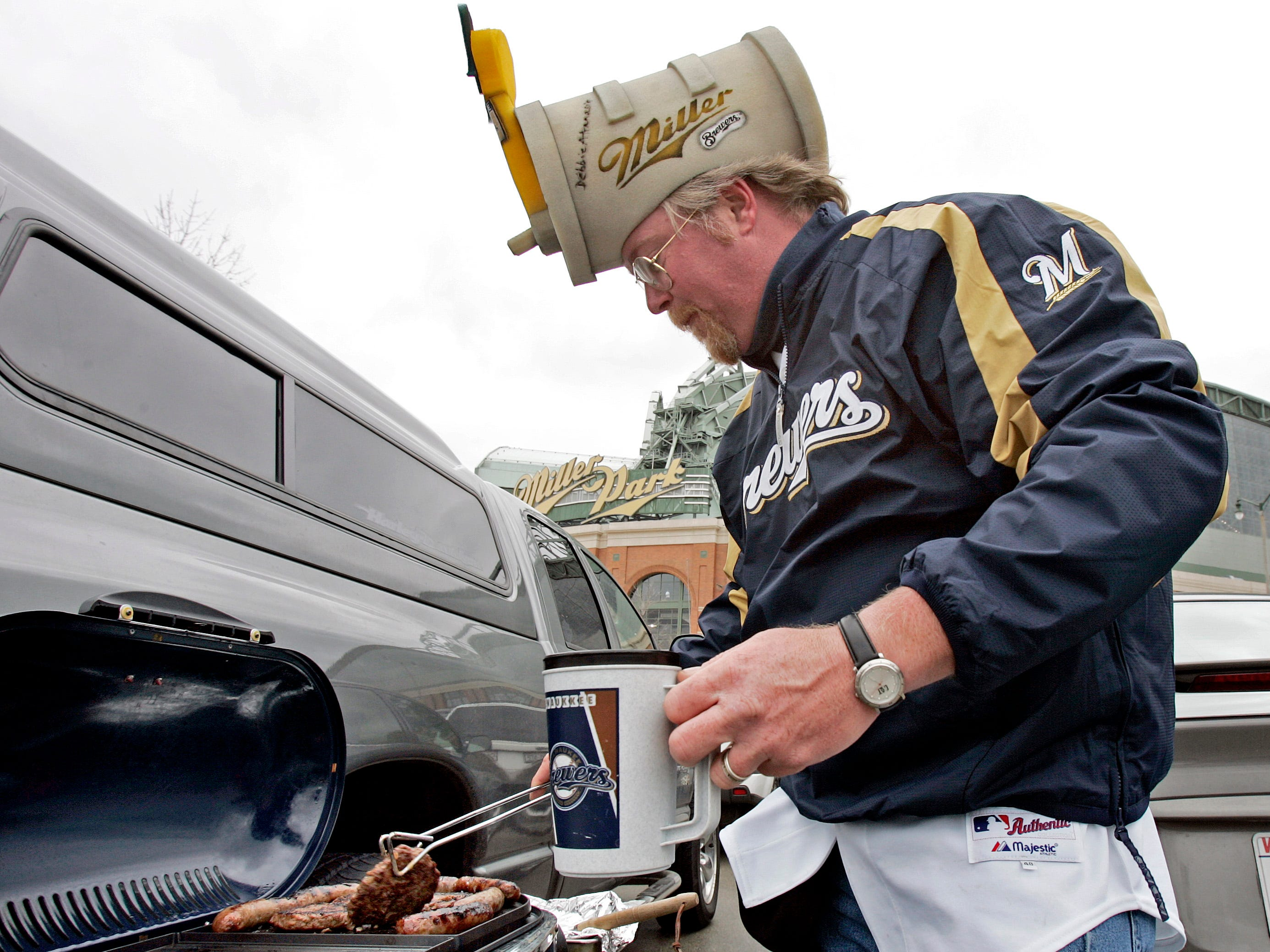 Paul Praeger of Menomonee Falls wears his foam Miller keg hat while he grills out before opening day at Miller Park Monday, April 3, 2006.
