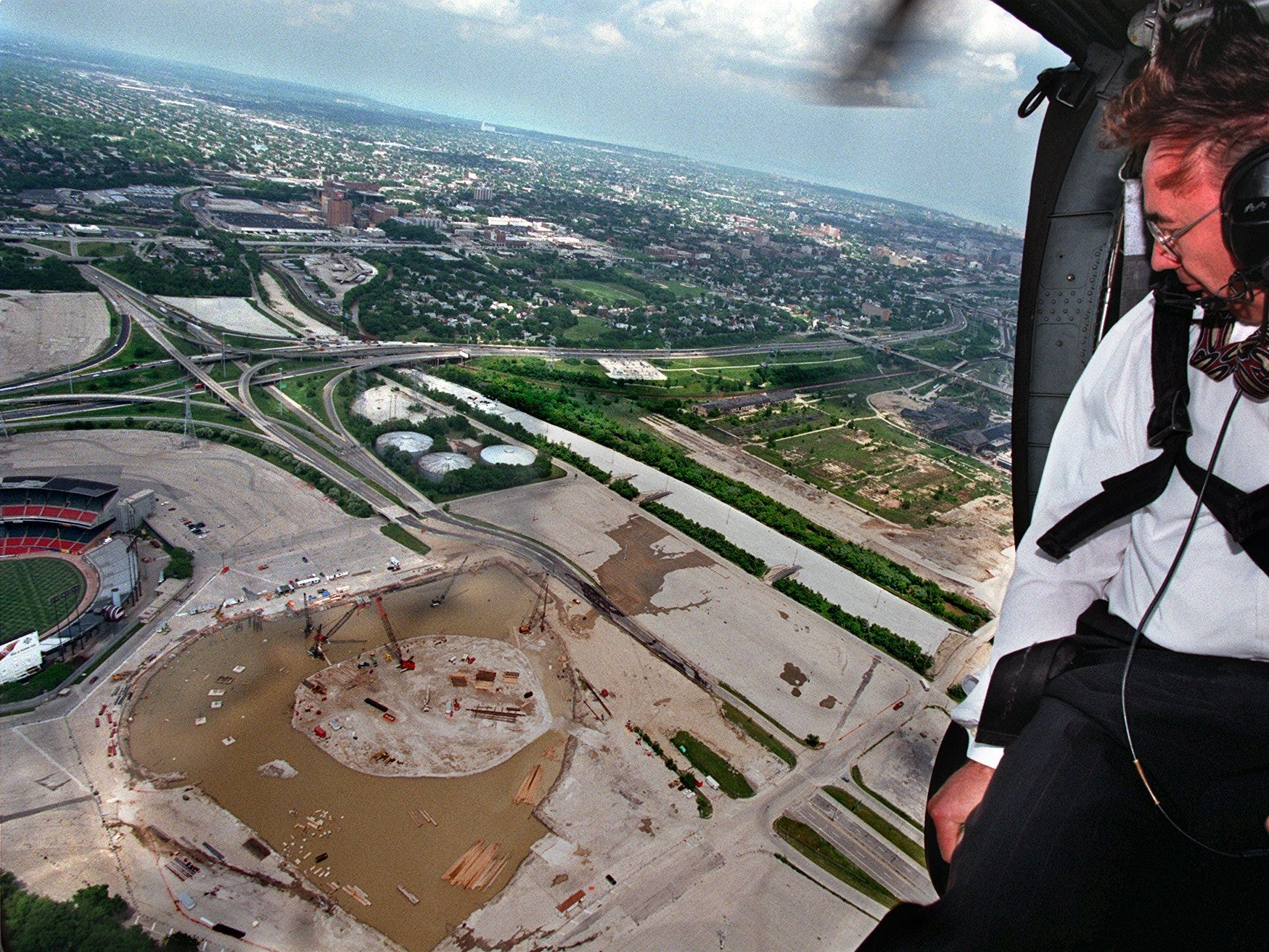 Gov. Tommy Thompson flies over water-soaked construction of the new Miller Park next to County Stadium while inspecting flood damage a near the Menomonee Valley.