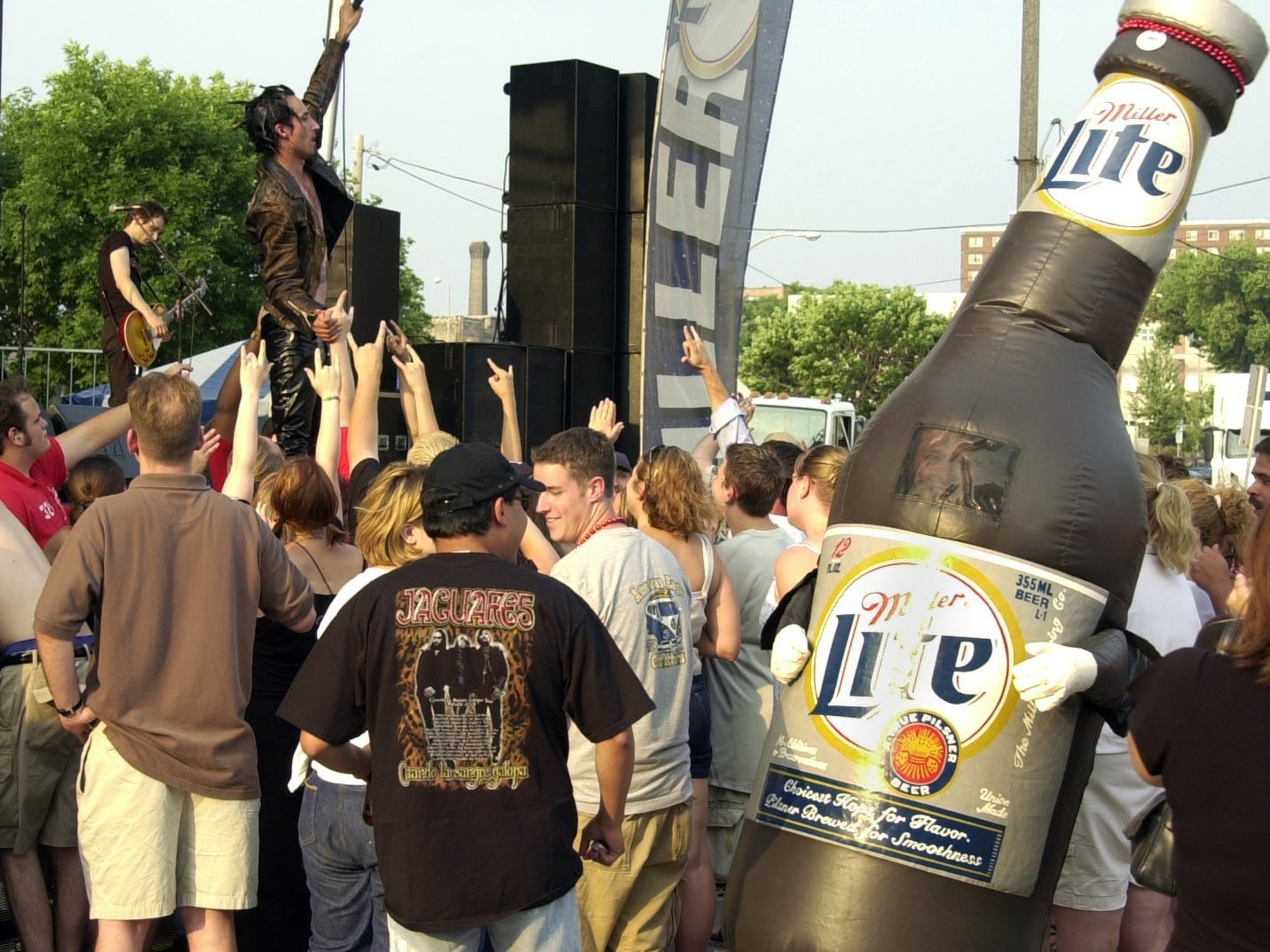 A man dressed as a beer bottle dances with others in 2002.