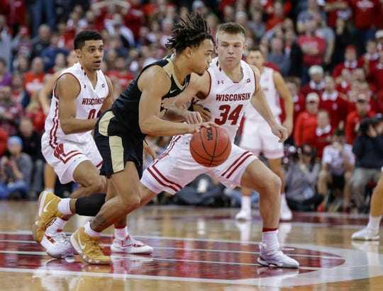 UW guards D'Mitrik Trice (left) and Brad Davison chase Purdue's Carsen Edwards in a recent game.