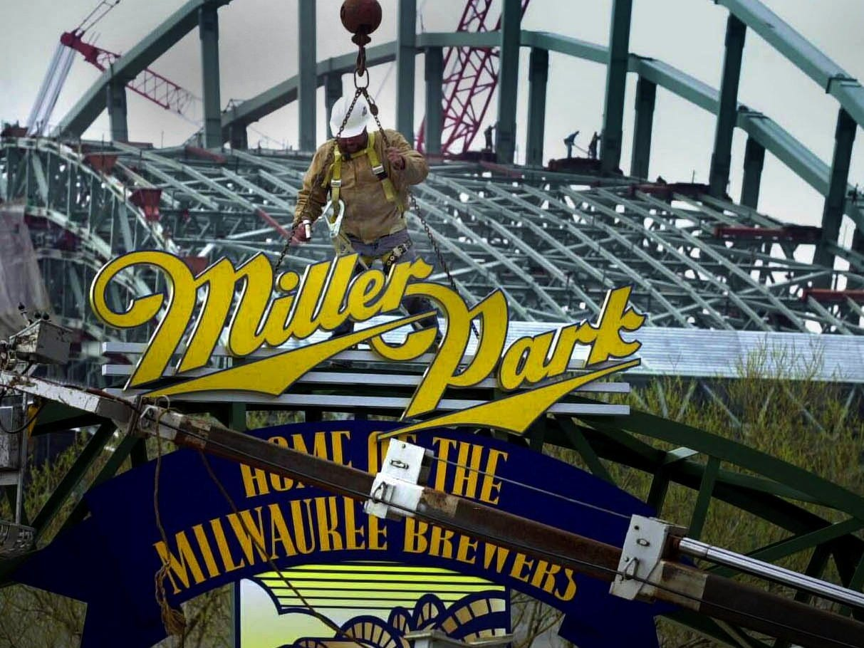 Carl Haase Jr. guides a Miller Park sign near the east parking lot of the new stadium as Miller Park roof work continues in the background.