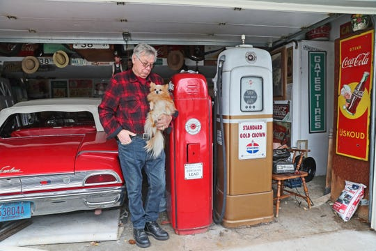 Vern Dahl of Cudahy collects gas station signs and other related antiques and recently was victimized by thieves who stole an old gas pump and soda machine on display outside his home. Dahl stands with his dog Popeye and antique gas pumps like the one stolen. The car is a 1960 Ford Galaxy Sunliner convertible.