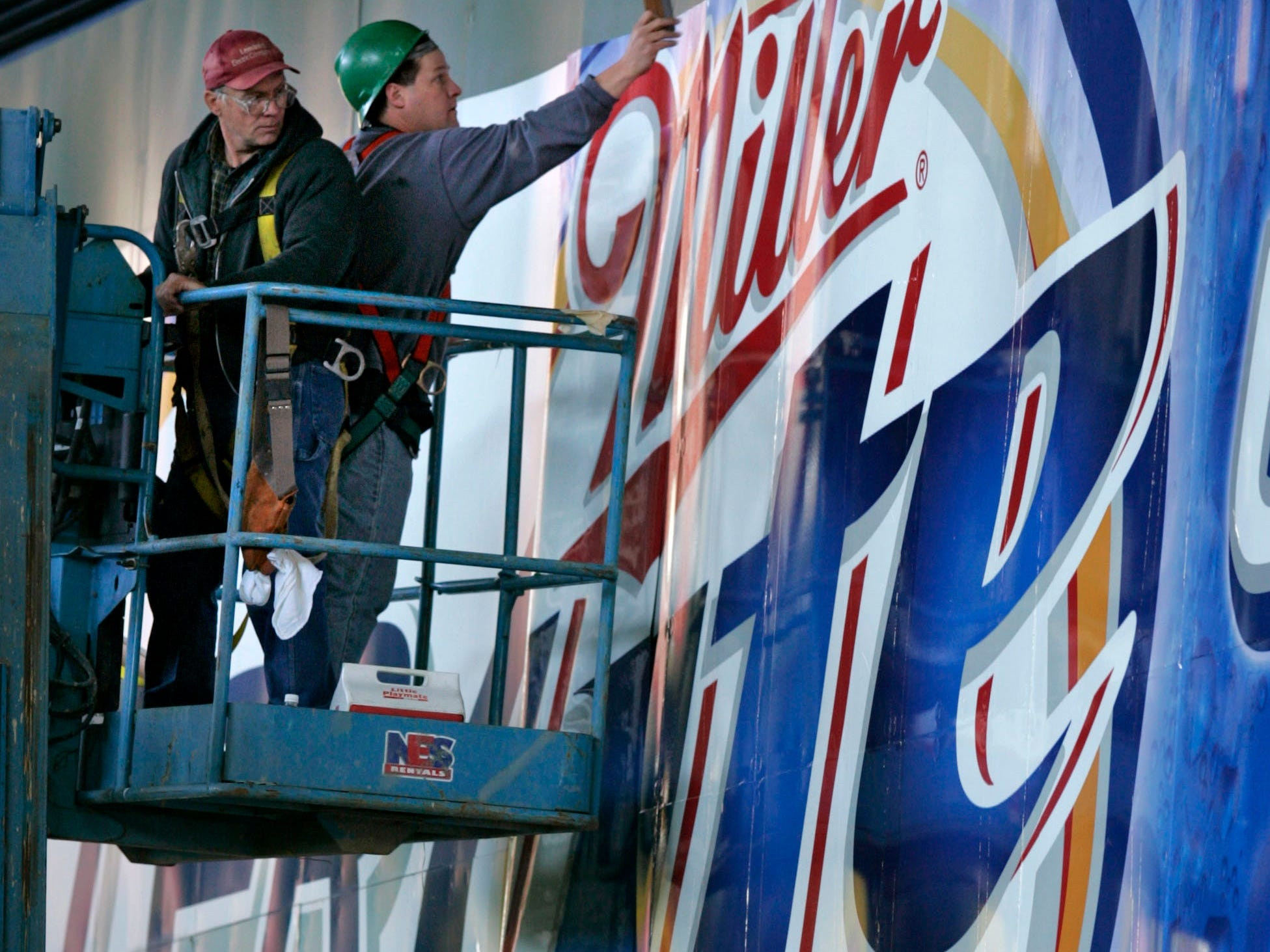 Paul Olson, right, and Dave Meinholz install one panel of many on a Miller advertisement  on the main scoreboard at Miller Park, Thursday, April 7, 2005.