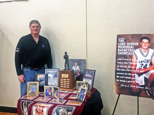 Former Marquette University player Jerry Homan poses with some of  his son Luke's trophies at the Luke Homan Showcase at Brookfield Central on Saturday. Luke, a standout athlete at Central, died in 2006.
