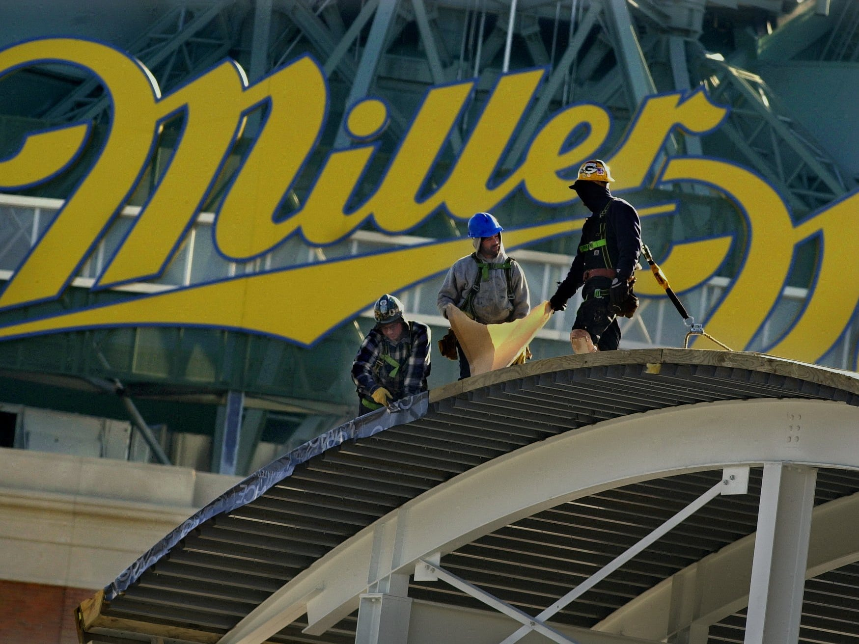 With Miller Park overshadowing their work, construction workers from Hunzinger Construction apply the roofing material to the $3.1 million facility at Miller Park known as Helfaer Field.