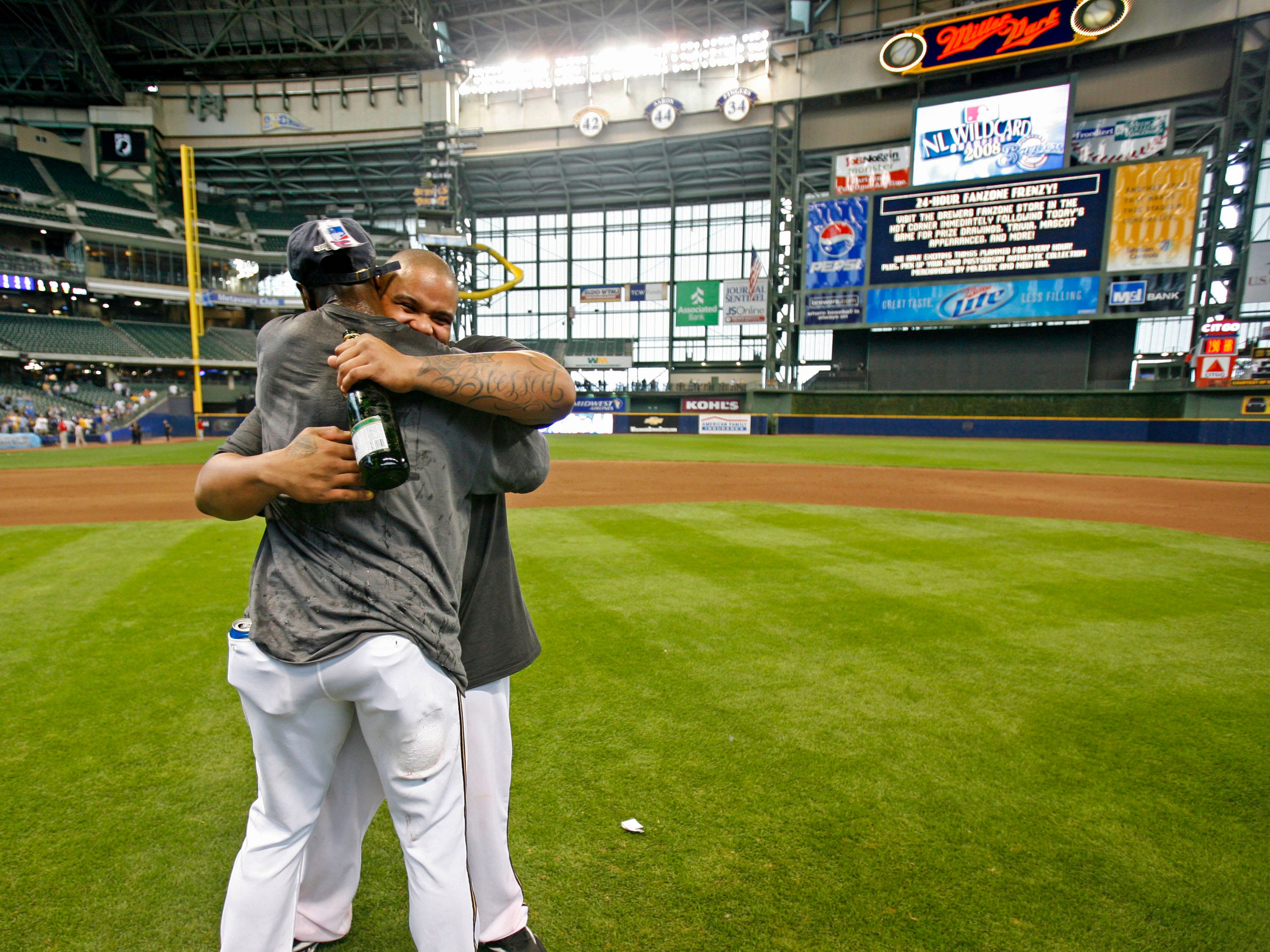 "Prince Fielder sports a ""blessed"" tattoo on his arm while holding champagne and getting a hug from Mike Cameron after a victory over the Cubs to win a  playoff wild card at Miller Park in 2008."