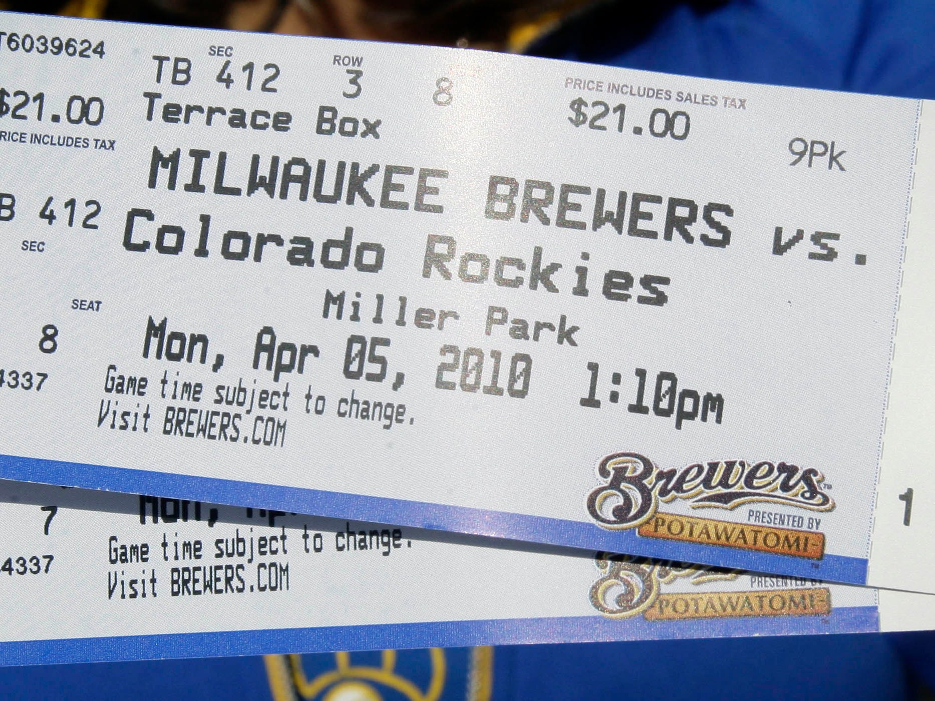 A fan displays her tickets before the Milwaukee Brewers home opener against the Colorado Rockies Monday, April 5, 2010.
