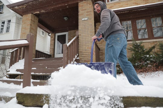 Jason Brenner, with V. P. Investors Property Management, removes snow from a home on the 3400 block of North 2nd Street in Milwaukee. A snowy, wintry mix is on its way, with storm totals possibly ranging up to 10 inches in some areas.