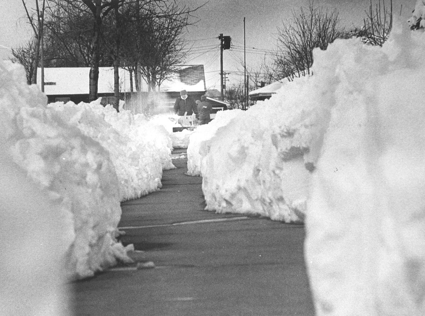 "Copy of a negative of a snowstorm in Milwaukee. On April 9th, 1973, 13 inches of snow fell. At was the second biggest April snowstorm in history up to that time. This photo was in the April 11th edition of the Journal with the caption ""A snowblower was used by Richard Schmidt in front of his home at 4452 N. 83rd St. as he cleared the walk adjacent to the jagged path shoveled by his neighbor."" Date is 4/11/1973 transparency folder #73521"